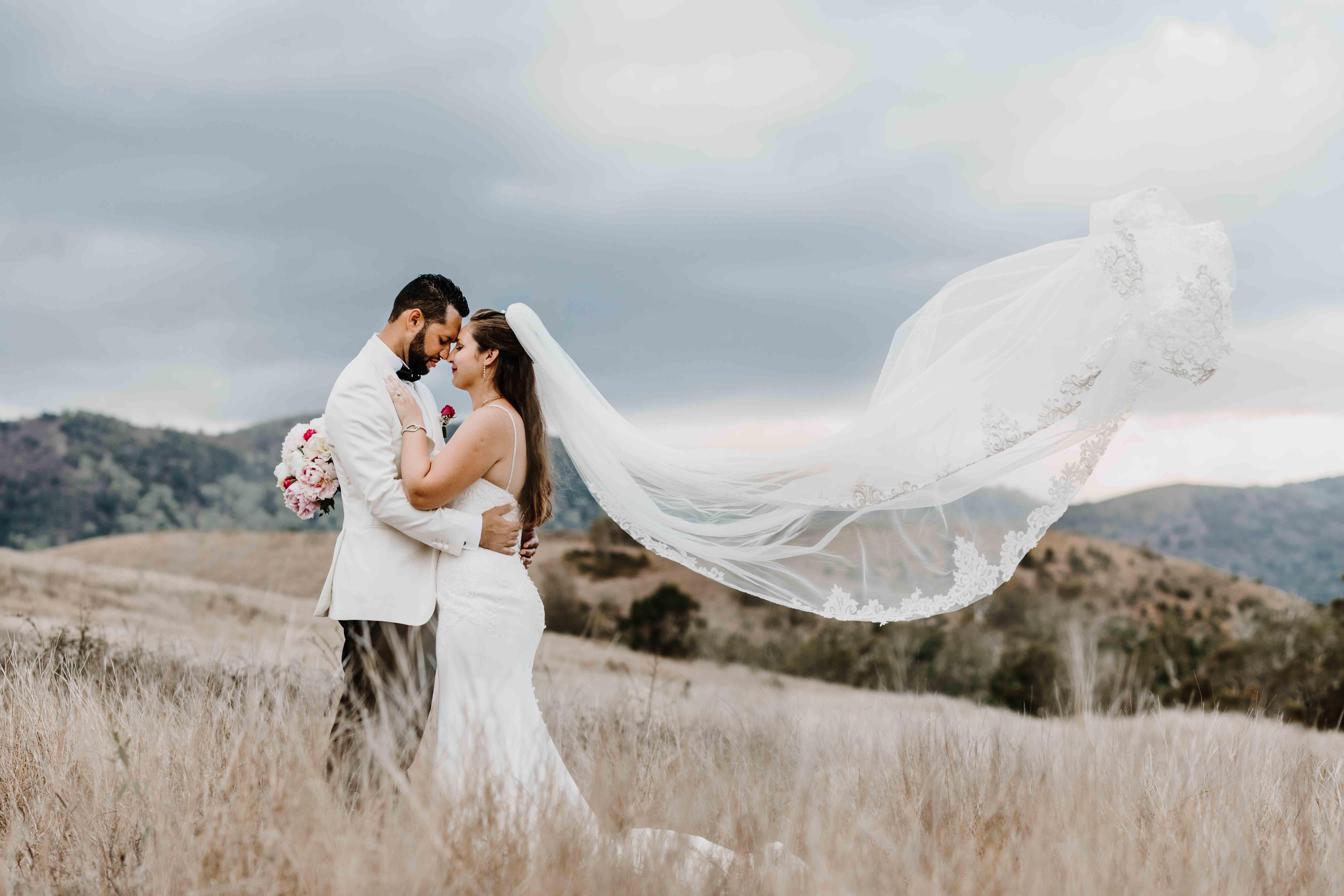 les mariés sont enlacés, tête à tête, les yeux fermés, le voile de la mariée vole dans les airs. le couple est dans les hautes herbes, mariage campagne, mariage champêtre boho