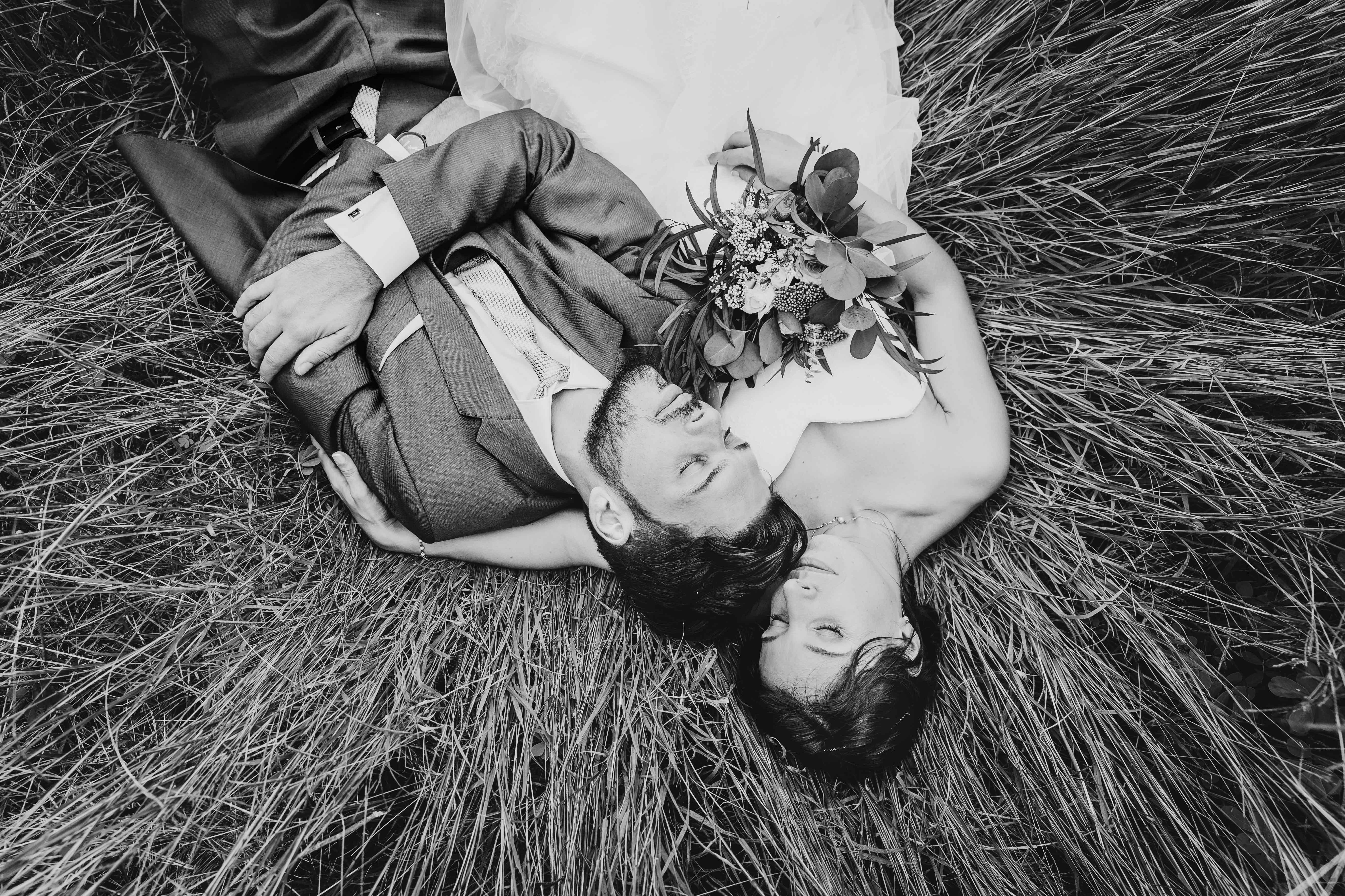 photo noir et blanc, les mariés sont allongés dans l'herbe les yeux fermés