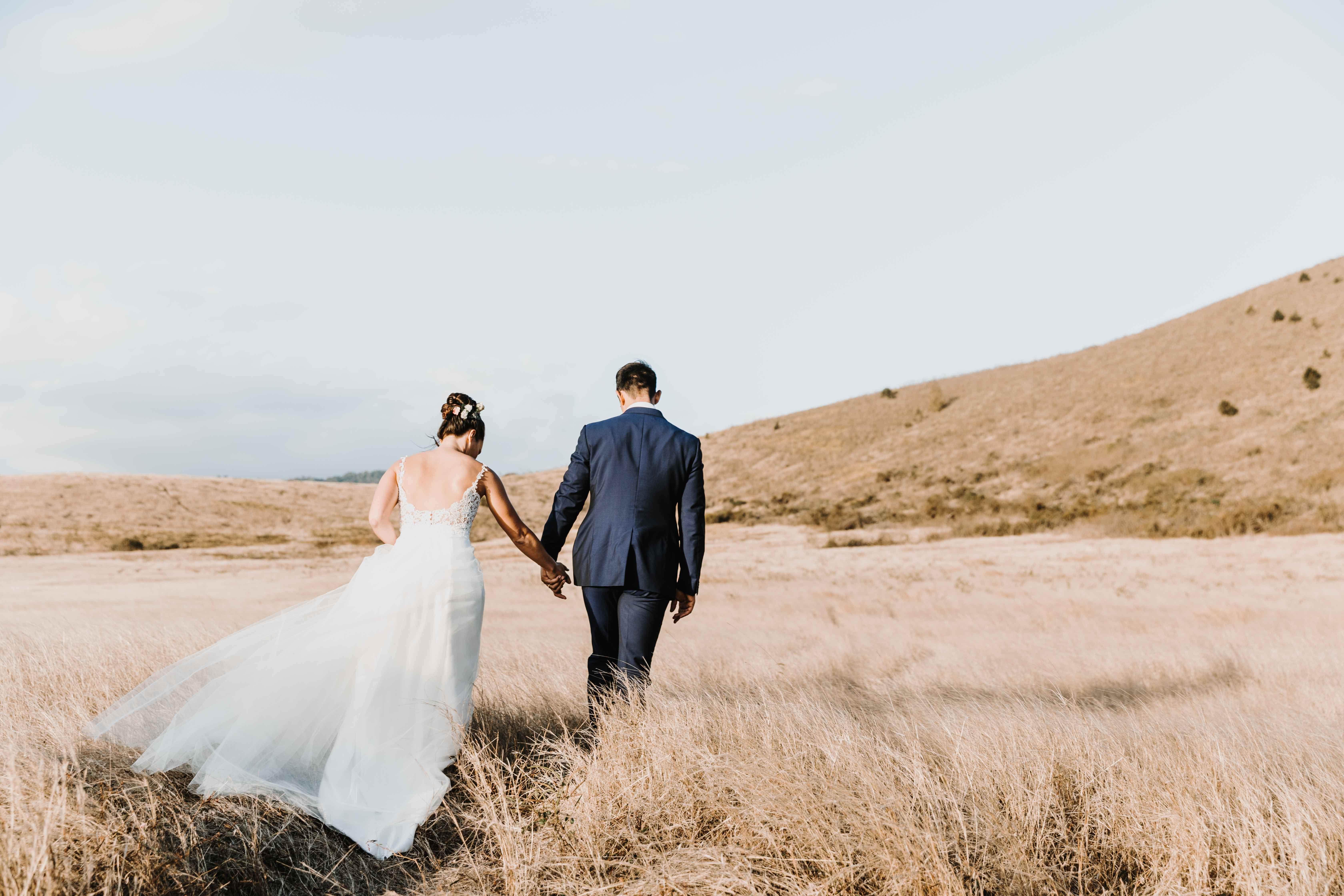 les mariés marchent main dans la main, de dos, dans les hautes herbes