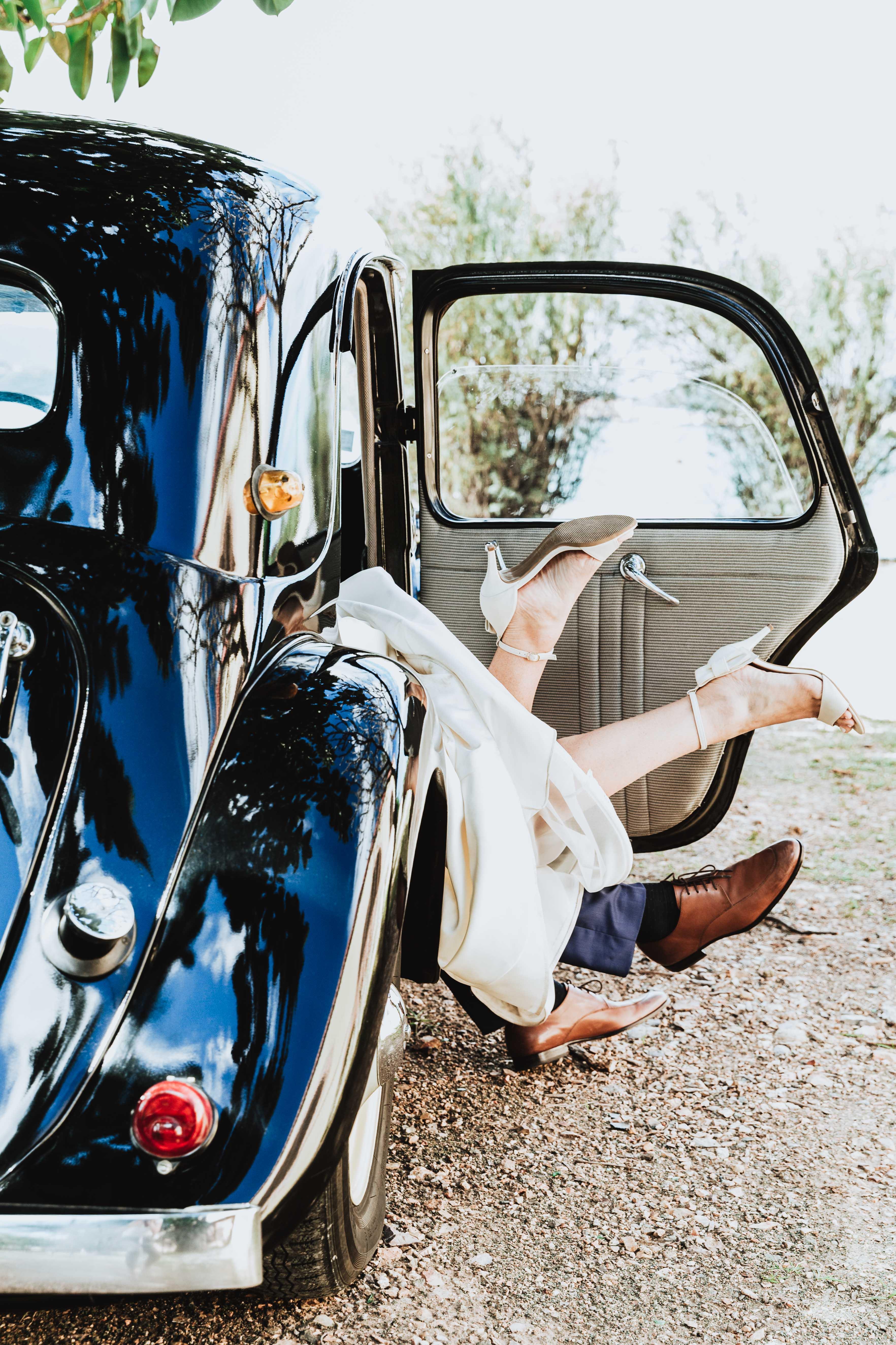 photo de mariage originale, fun. les pieds des marias sortent d'une voiture rétro