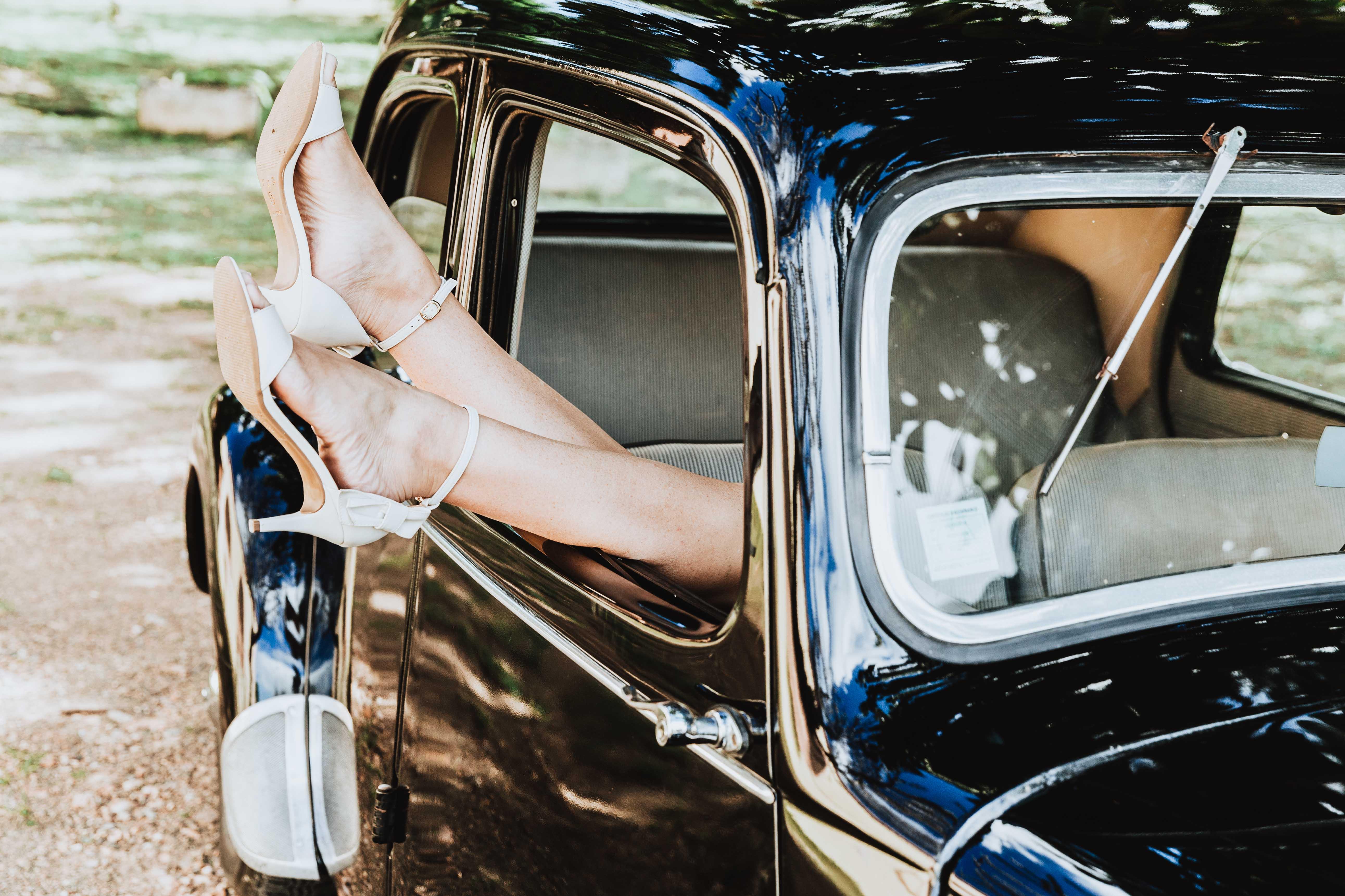 photo de mariage originale. les chaussures de la mariés dépassent de la fenêtre d'une voiture vintage