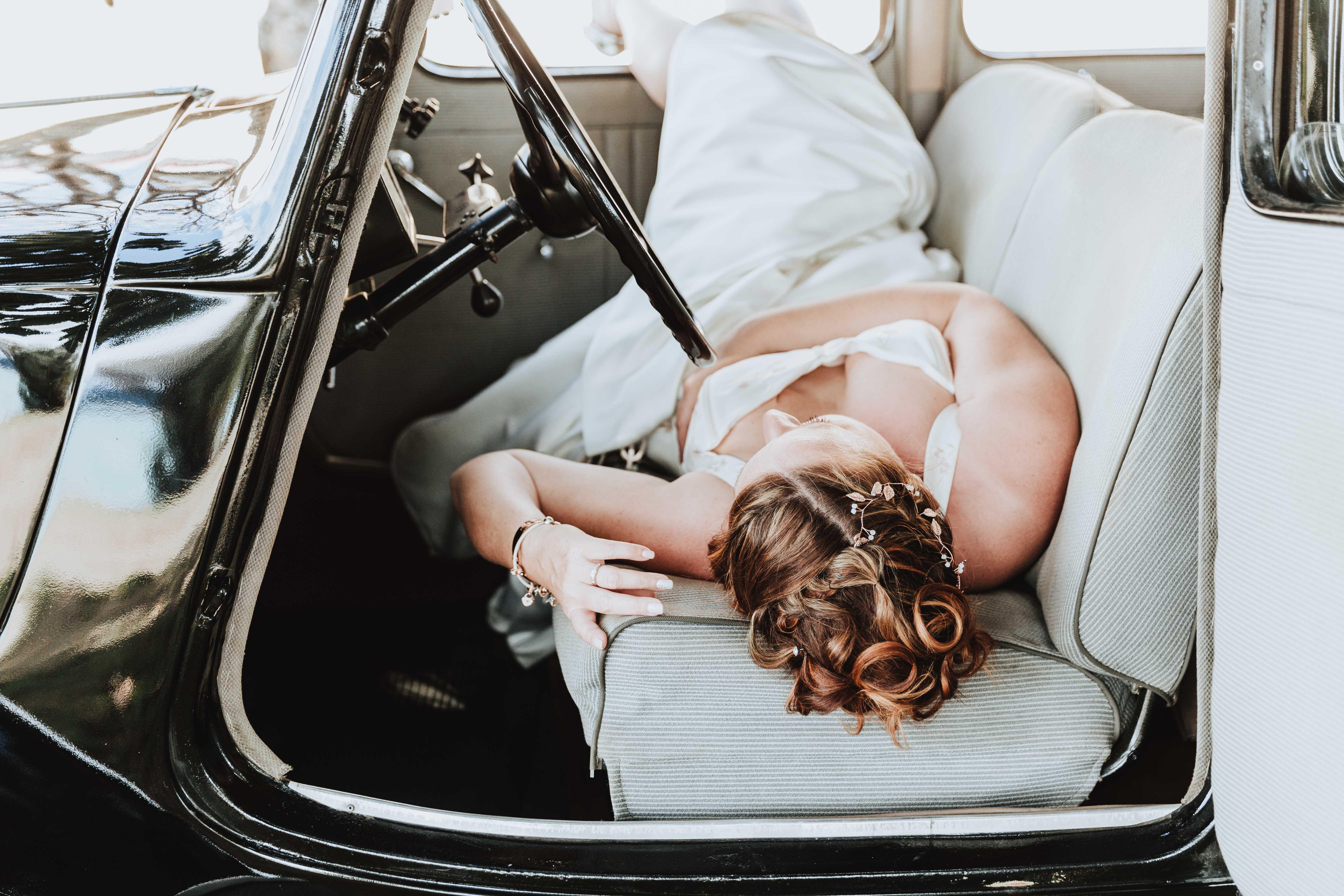 la mariée est allongée dans une voiture rétro