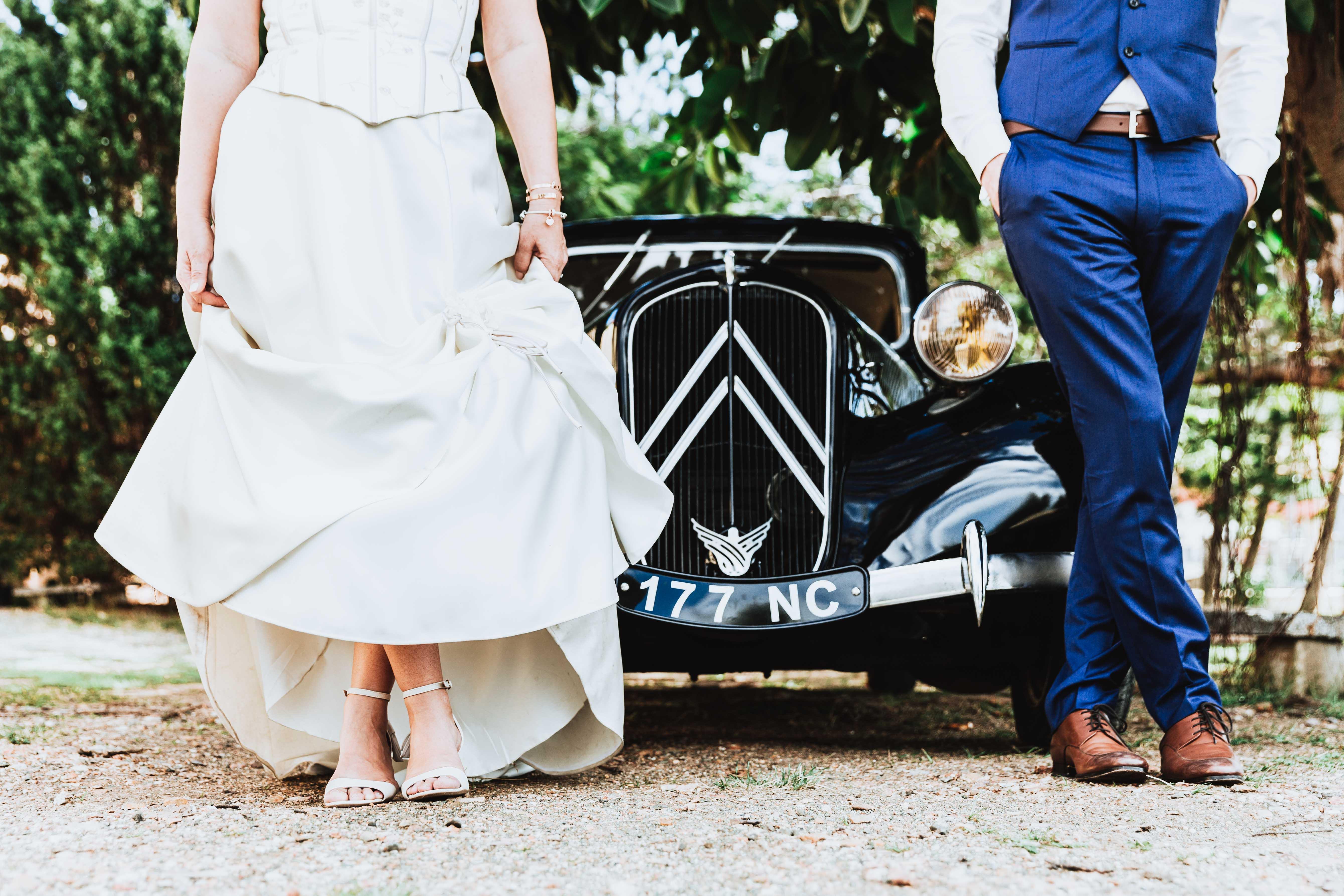 détail des jambes des mariés devant une voiture vintage
