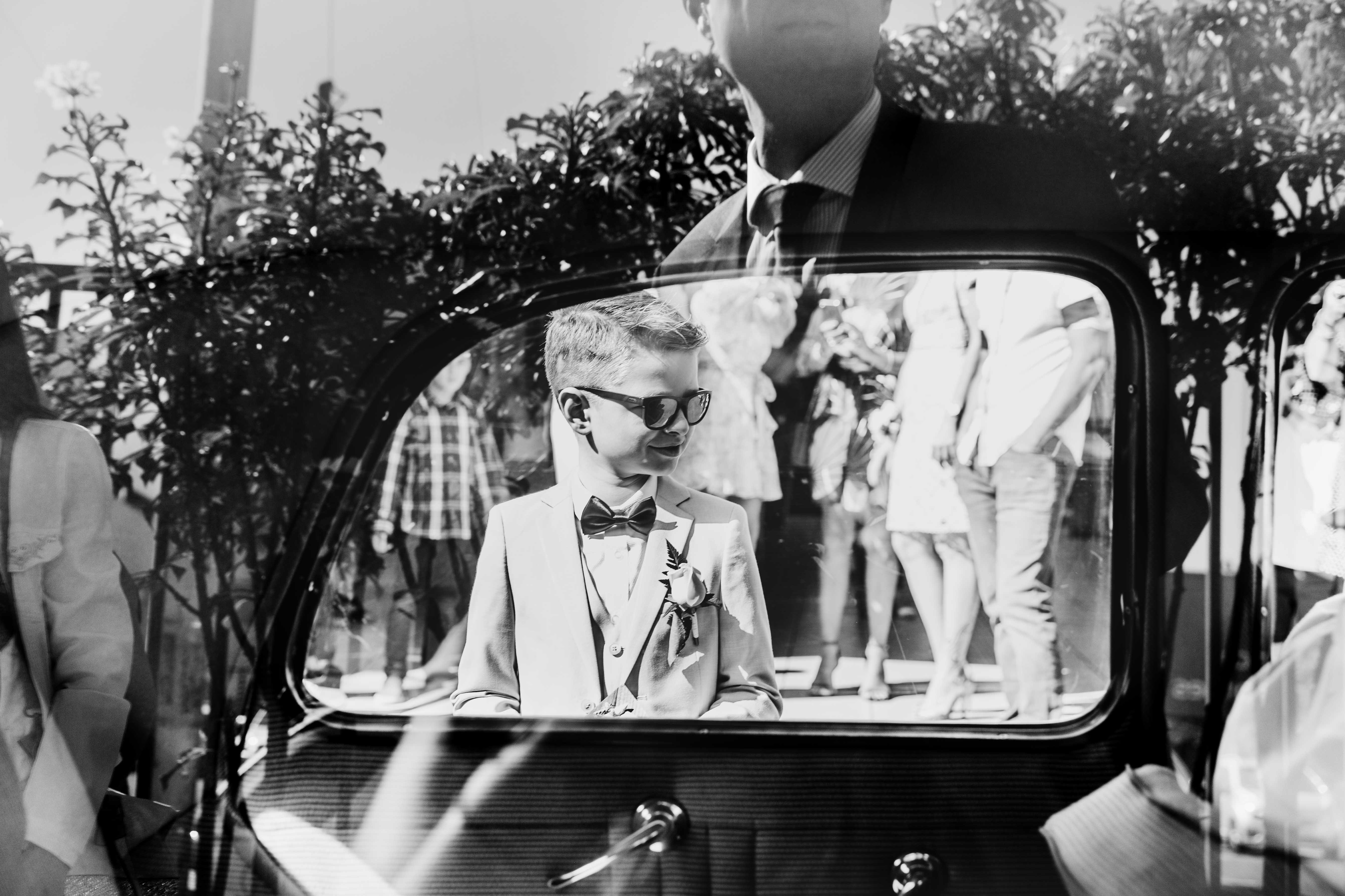 le fils des mariés au travers les fenêtres de la voiture du cortège