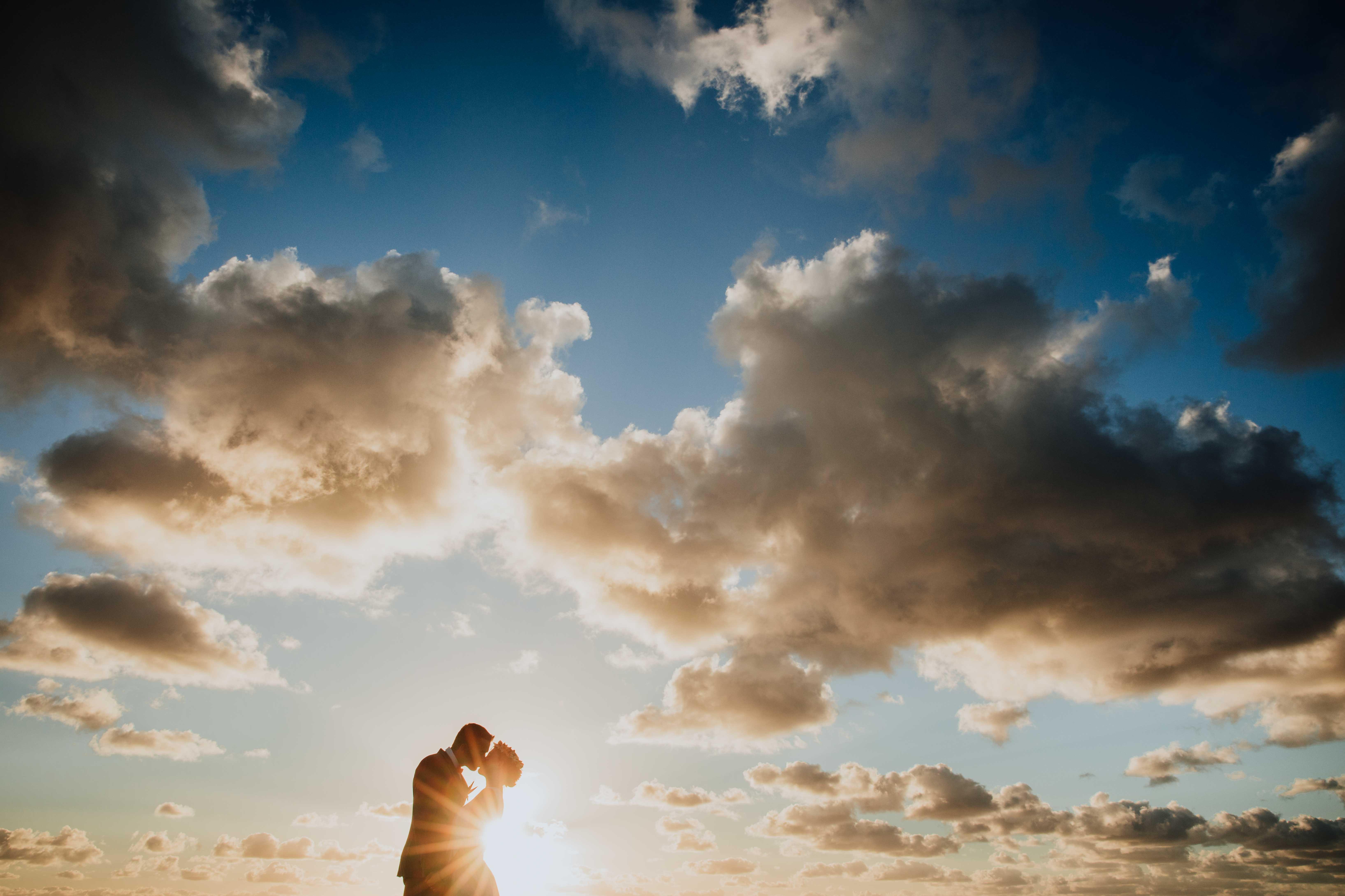 coucher de soleil, silhouette des mariés qui s'embrassent.