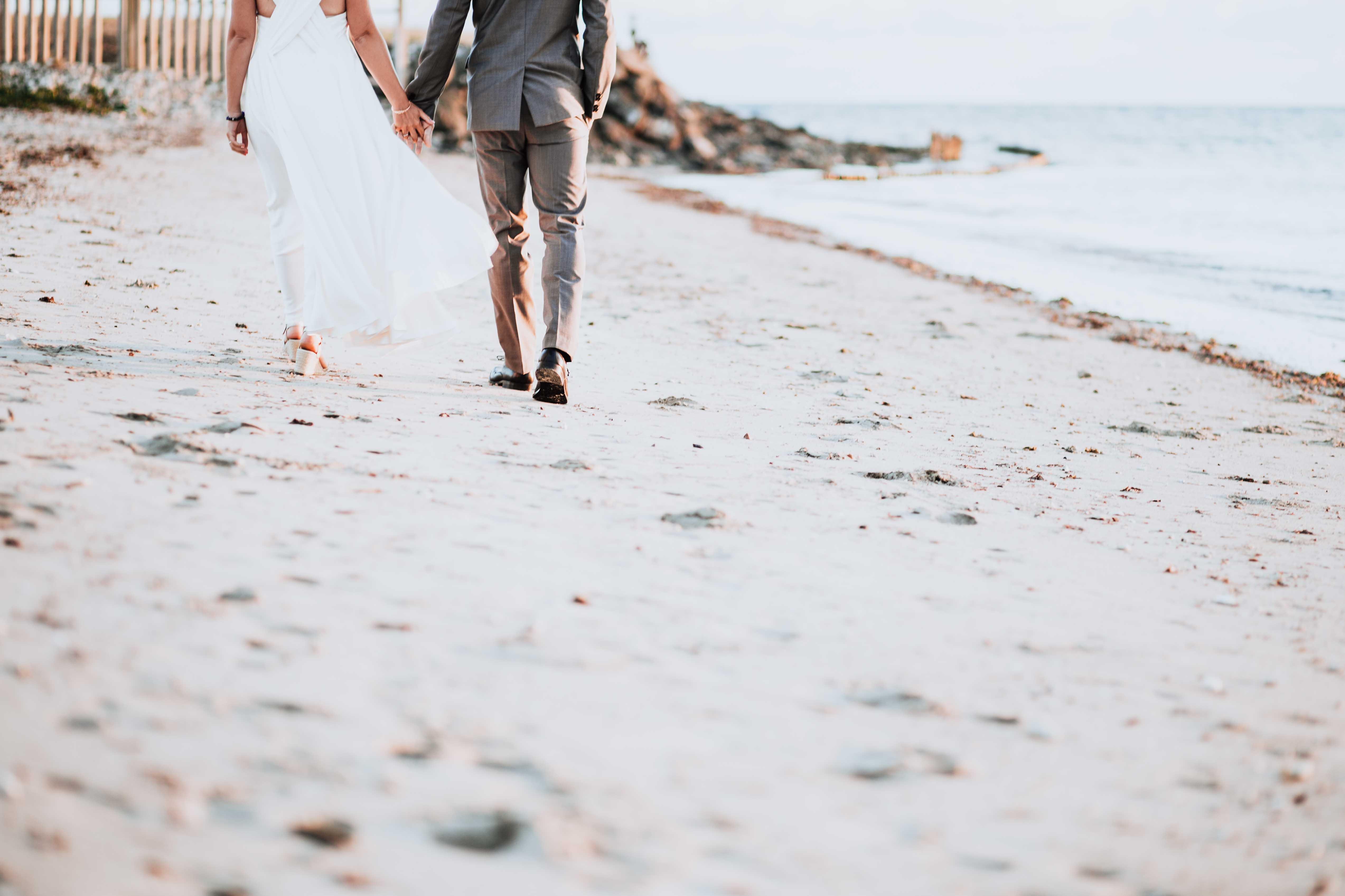 les mariés marchent de dos sur la plage