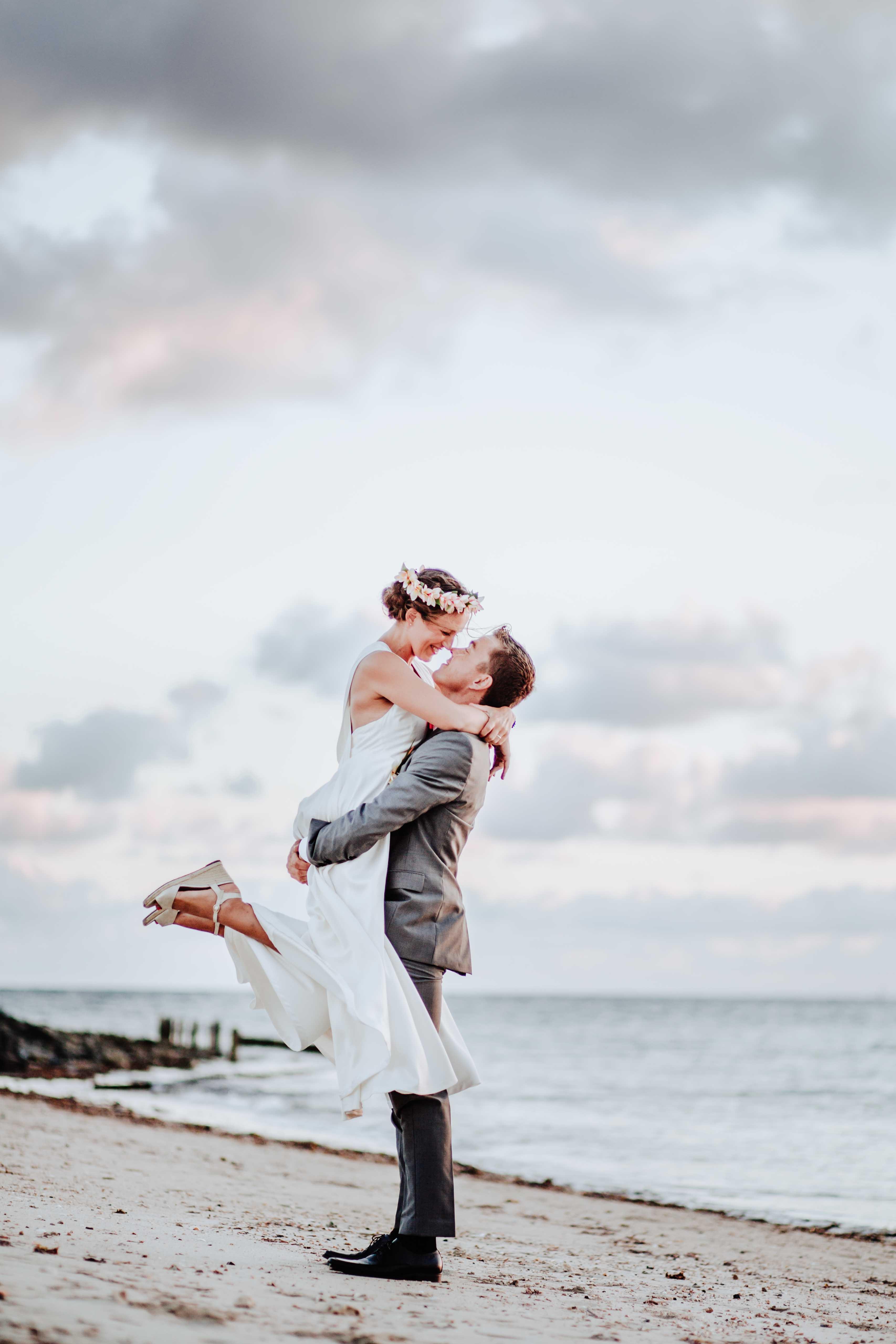 le marié porte la mariée sur la plage, il s'embrassent