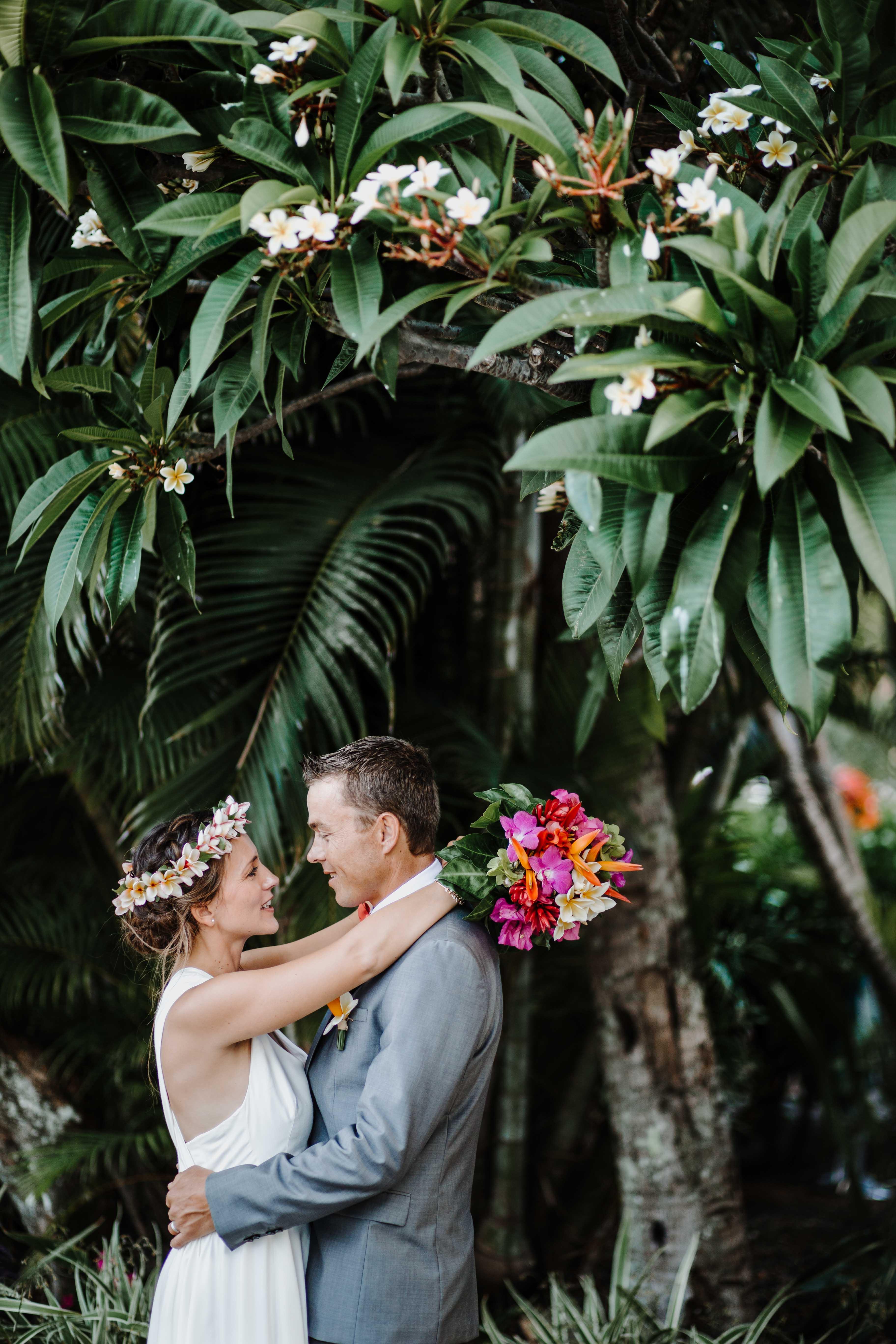 les mariés sont enlacés et se regardent sous un arbre tropical, frangipanier
