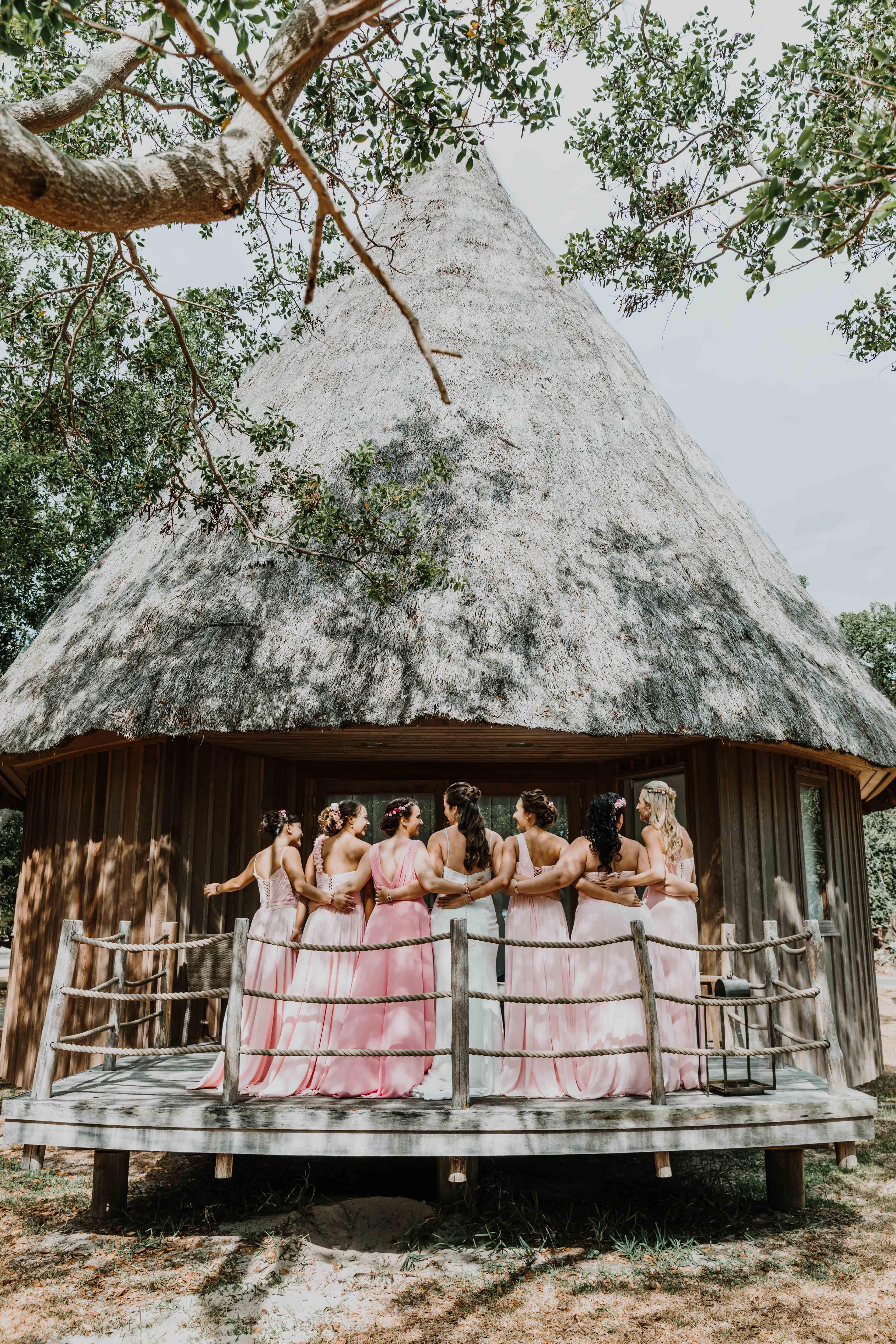 la mariée et les demoiselles d'honneur sont en ligne, de dos, et se regardent sur la terrasse d'un bungalow en bois en bord de plage