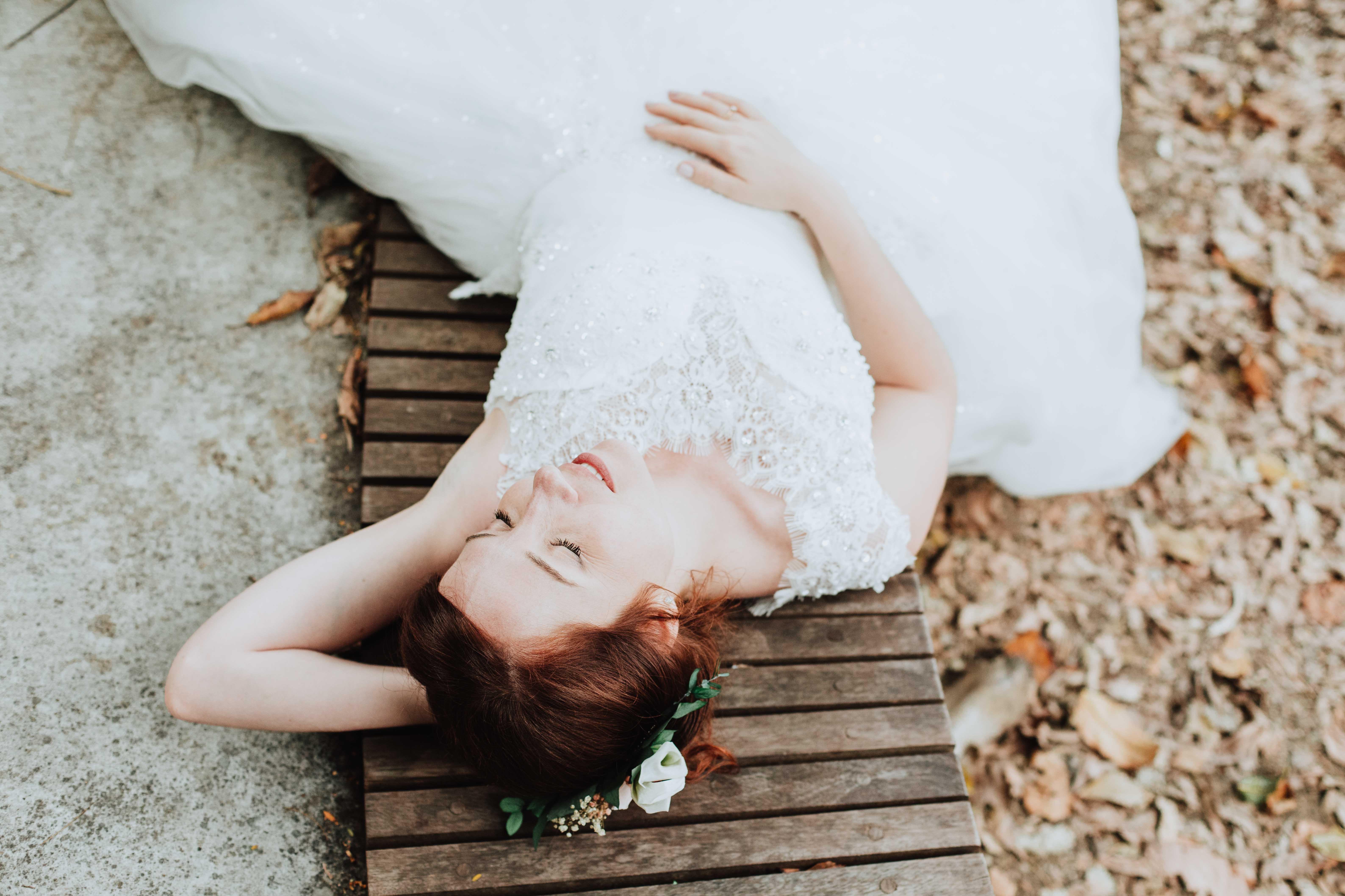la mariée est allongée au sol, les yeux fermés