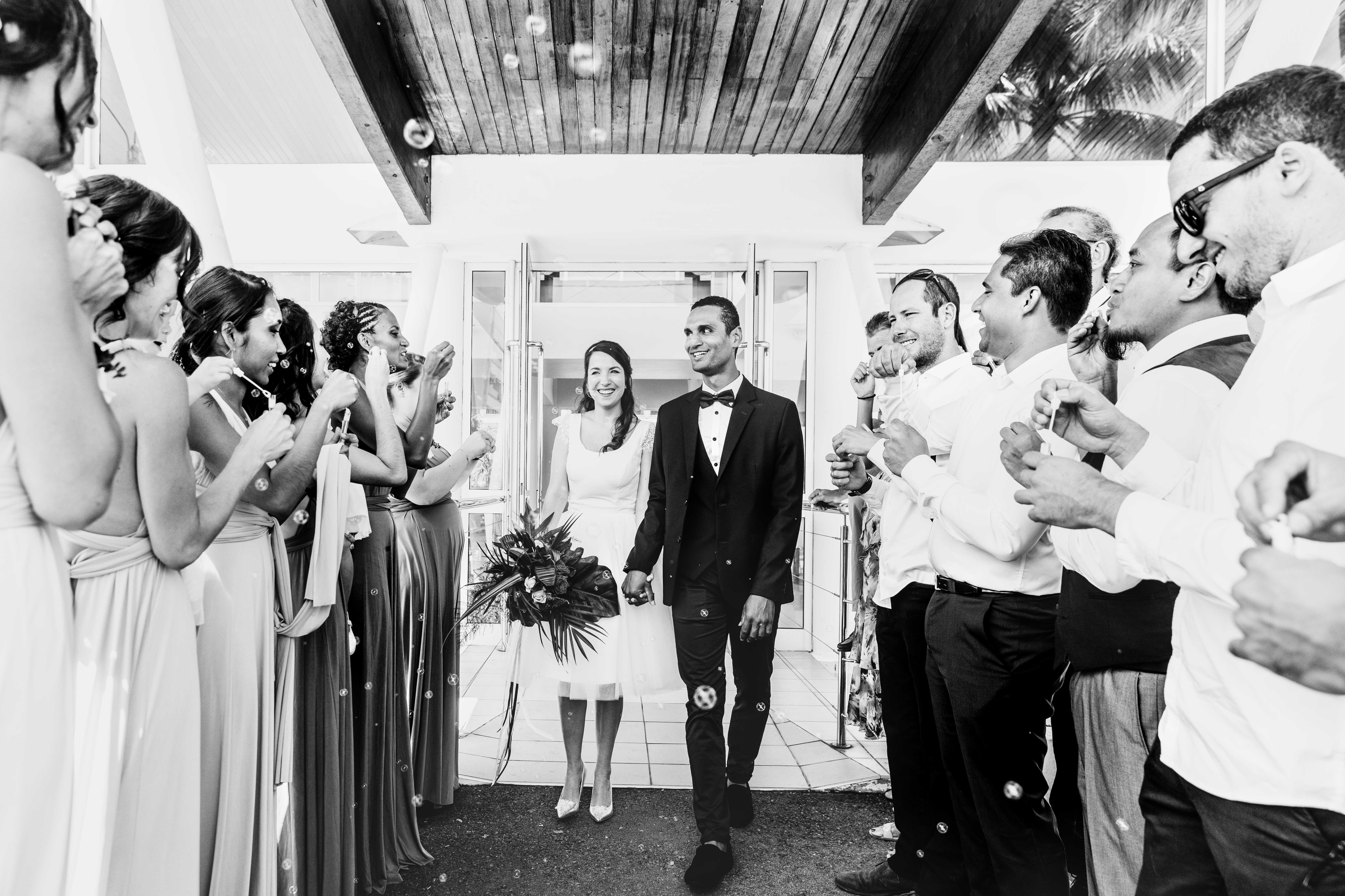 photo noir et blanc, les mariés sortent de la mairie, les invités soufflent des bulles