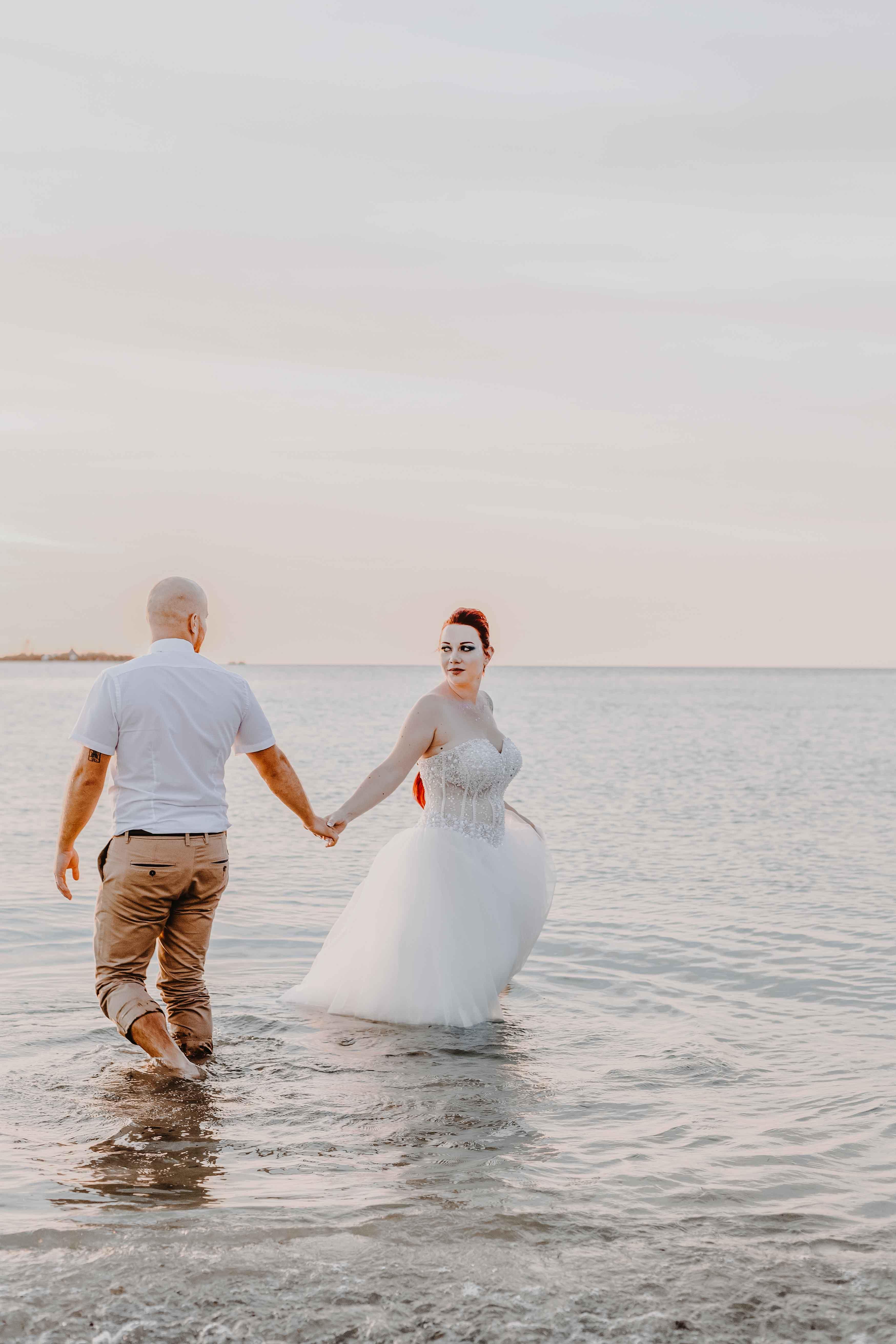 séance photo crash the dress dans la mer mariage . les mariés dansent les pieds dans l'eau