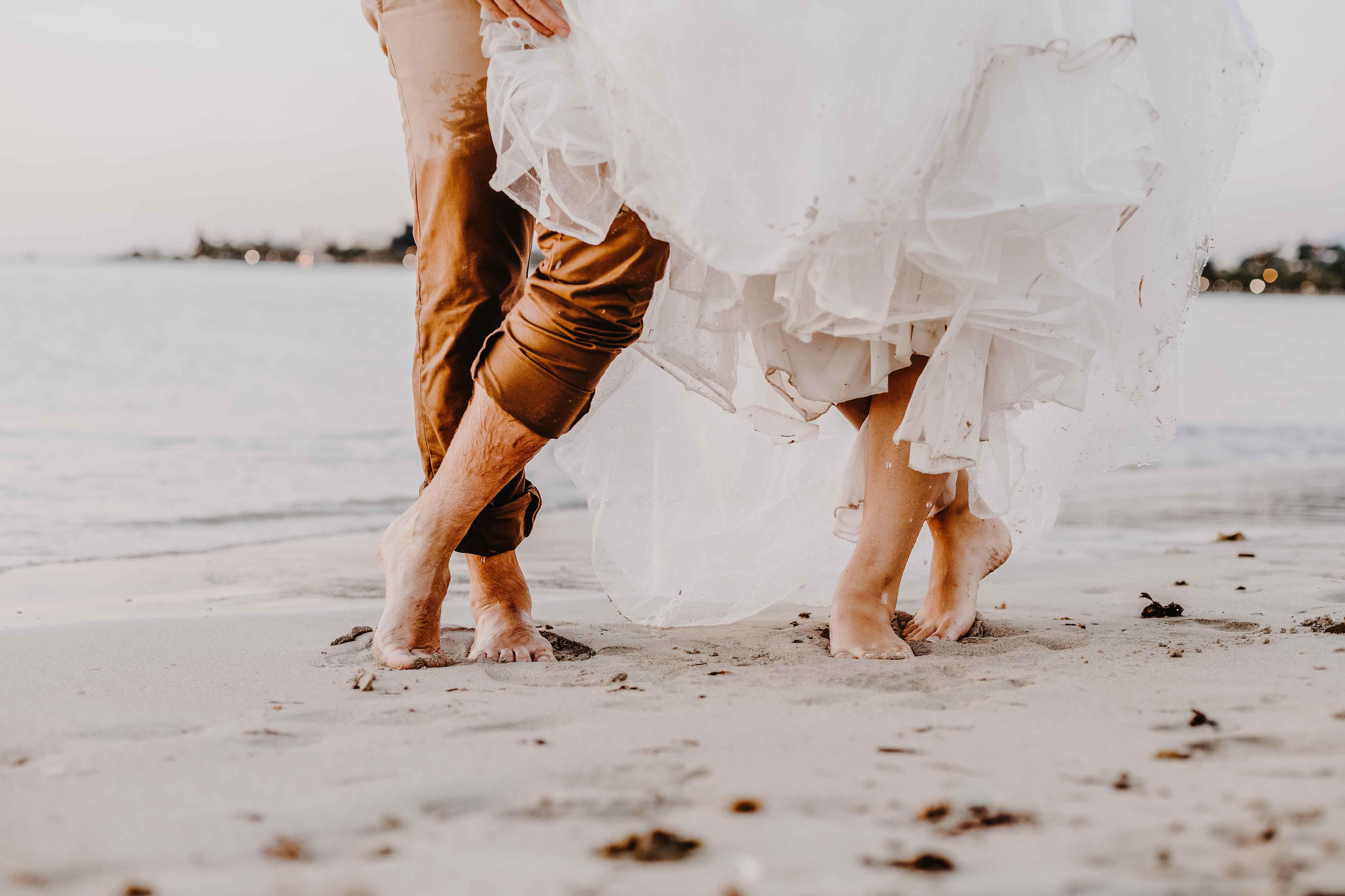 séance photo crash the dress dans la mer mariage . détail des pieds des mariés dans le sable, la robe et le costume sont mouillés