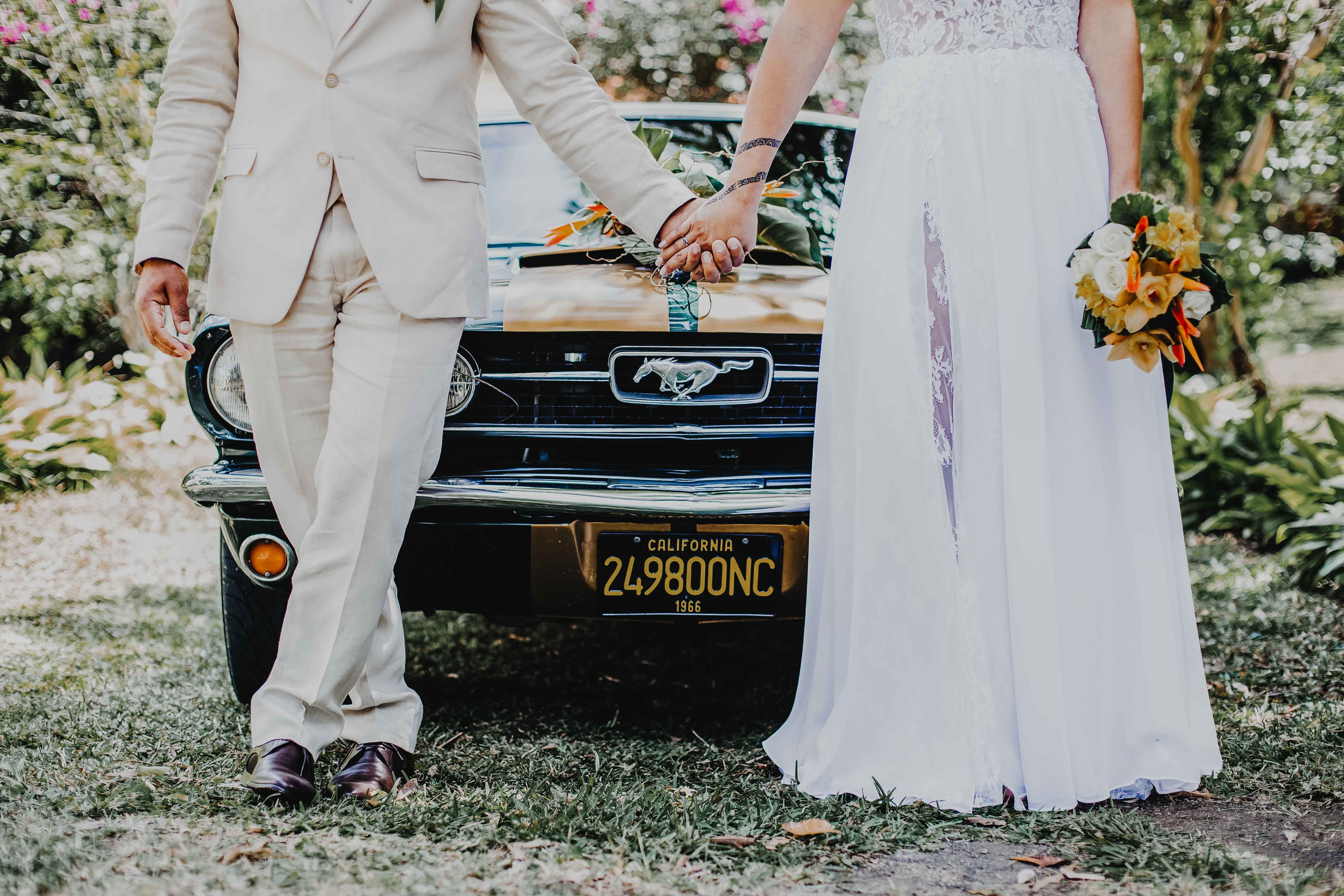 mariage rétro vintage. les mariés sont debout devant une voiture mustang vintage