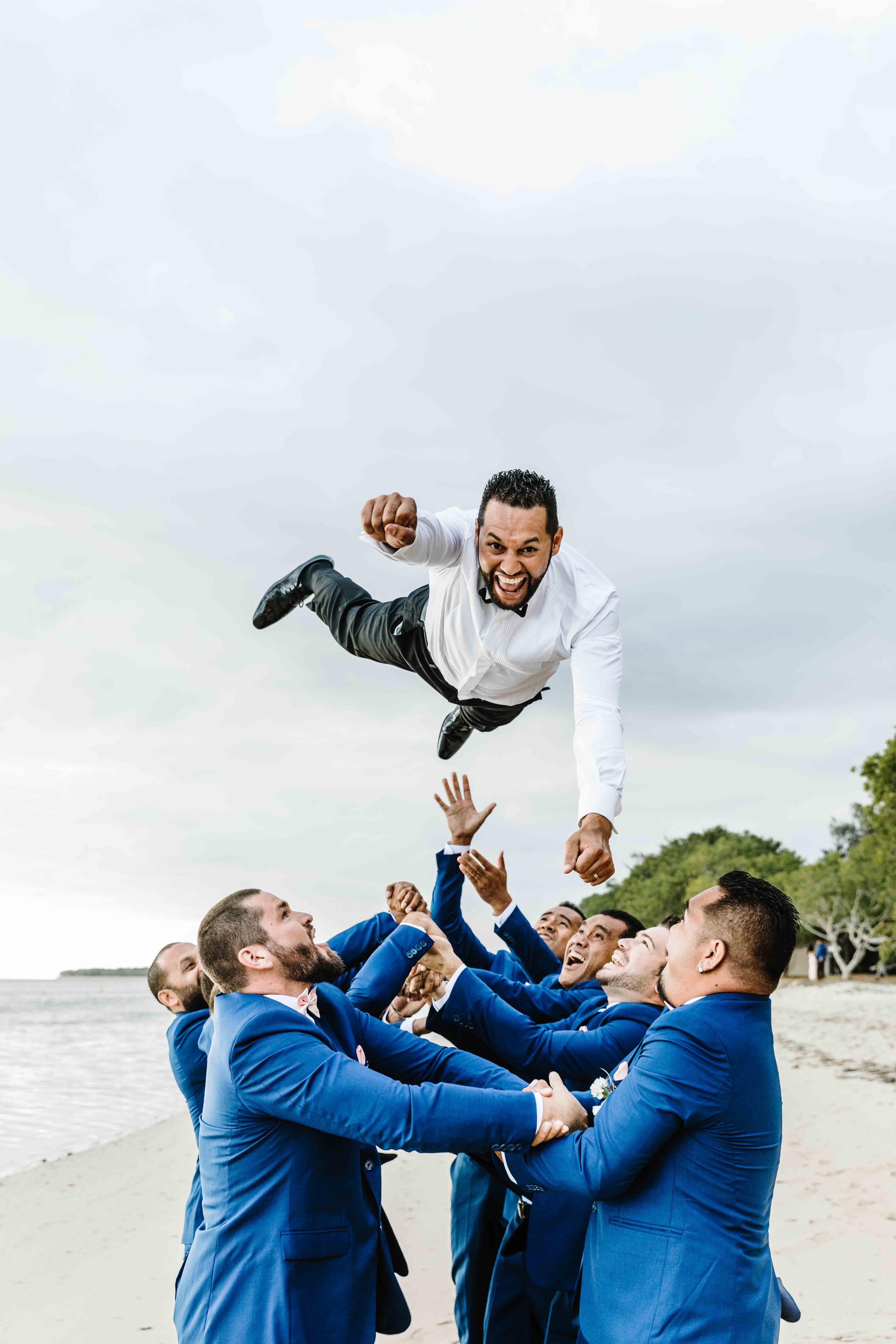 photo de mariage fun. les garçons d'honneur lancent la marié en l'air