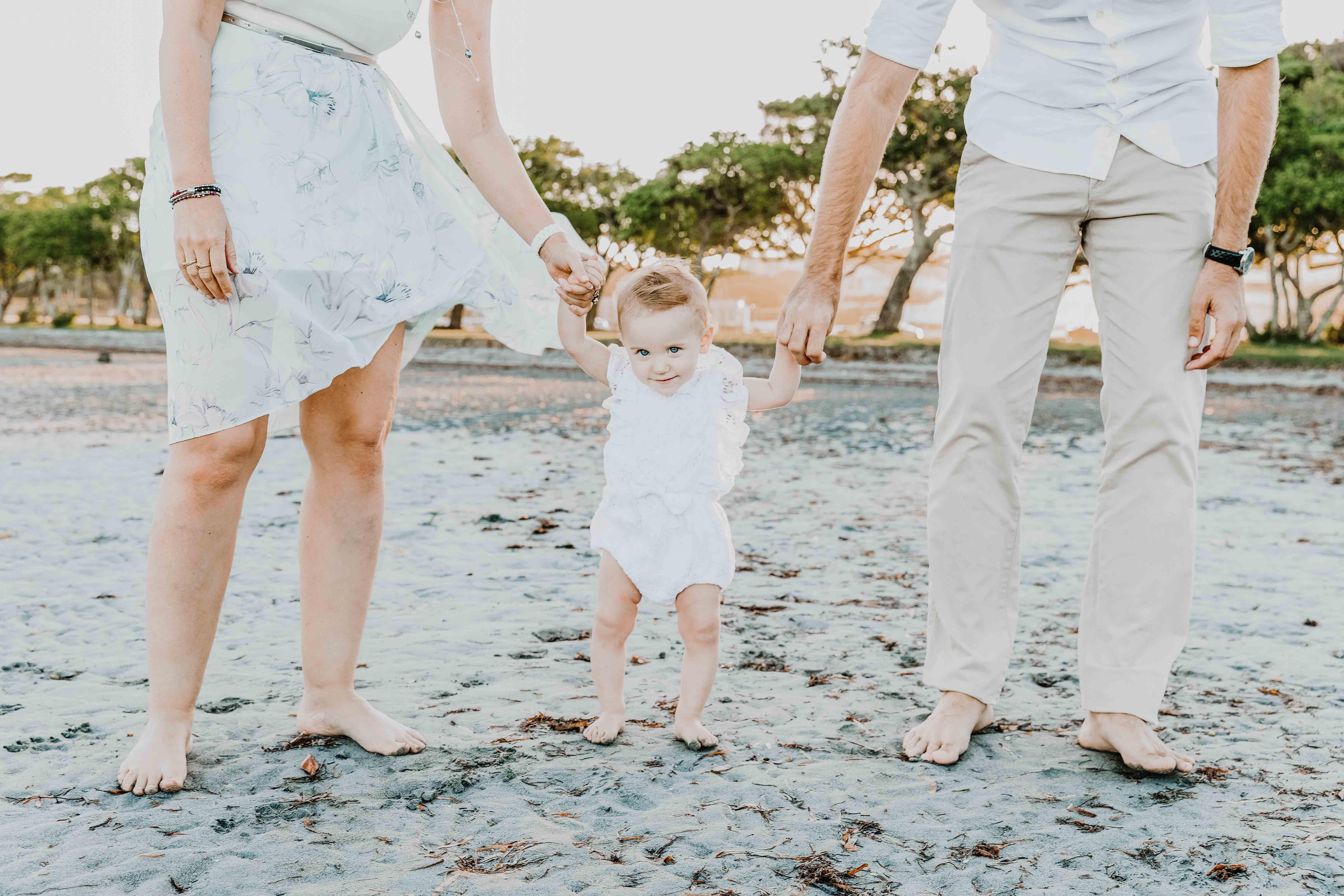 séance photo famille à la plage. les parents sont debout et aident bébé à marcher