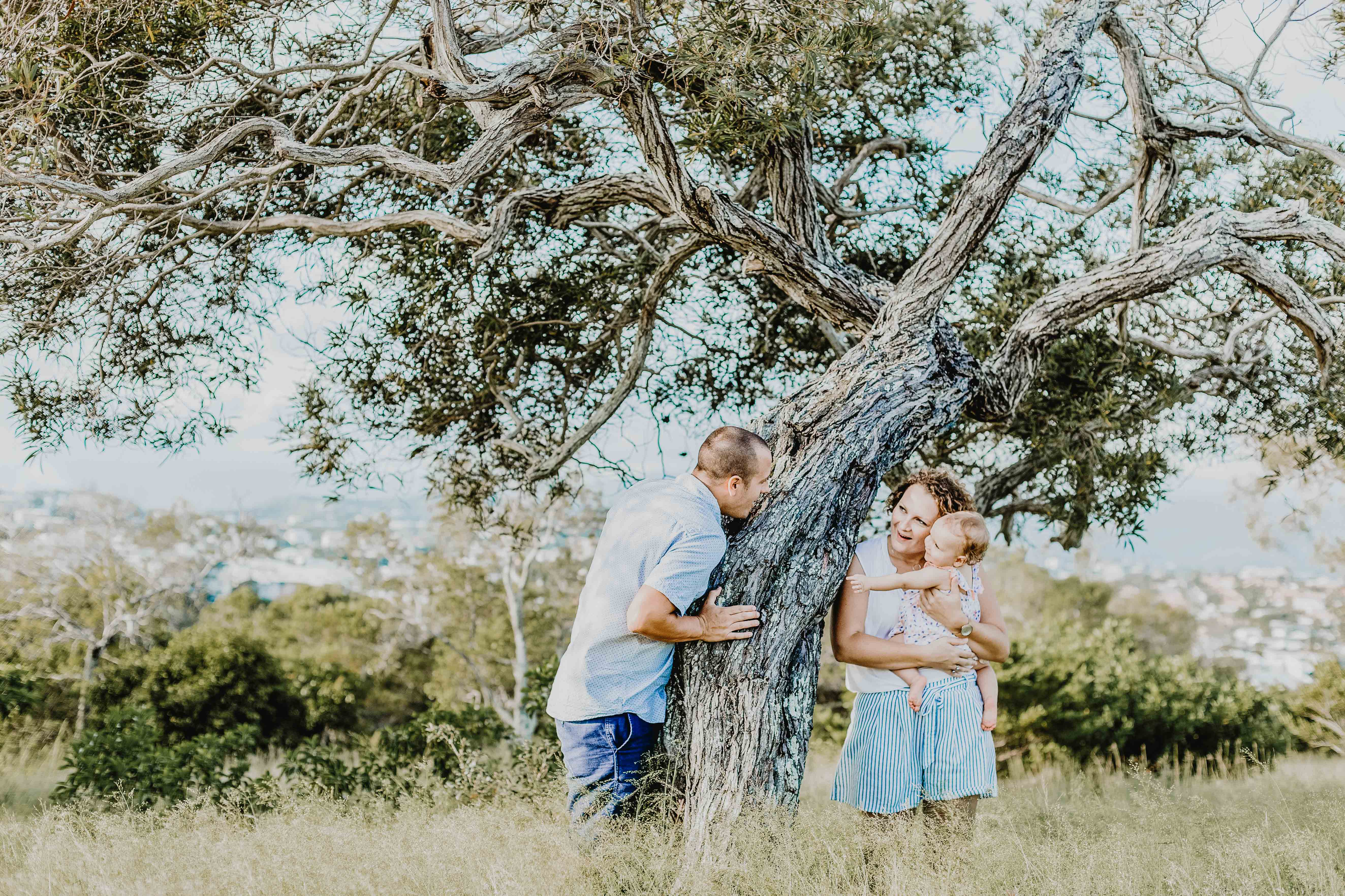 séance photo famille lifestyle en extérieur. les parents portent bébé près d'un arbre
