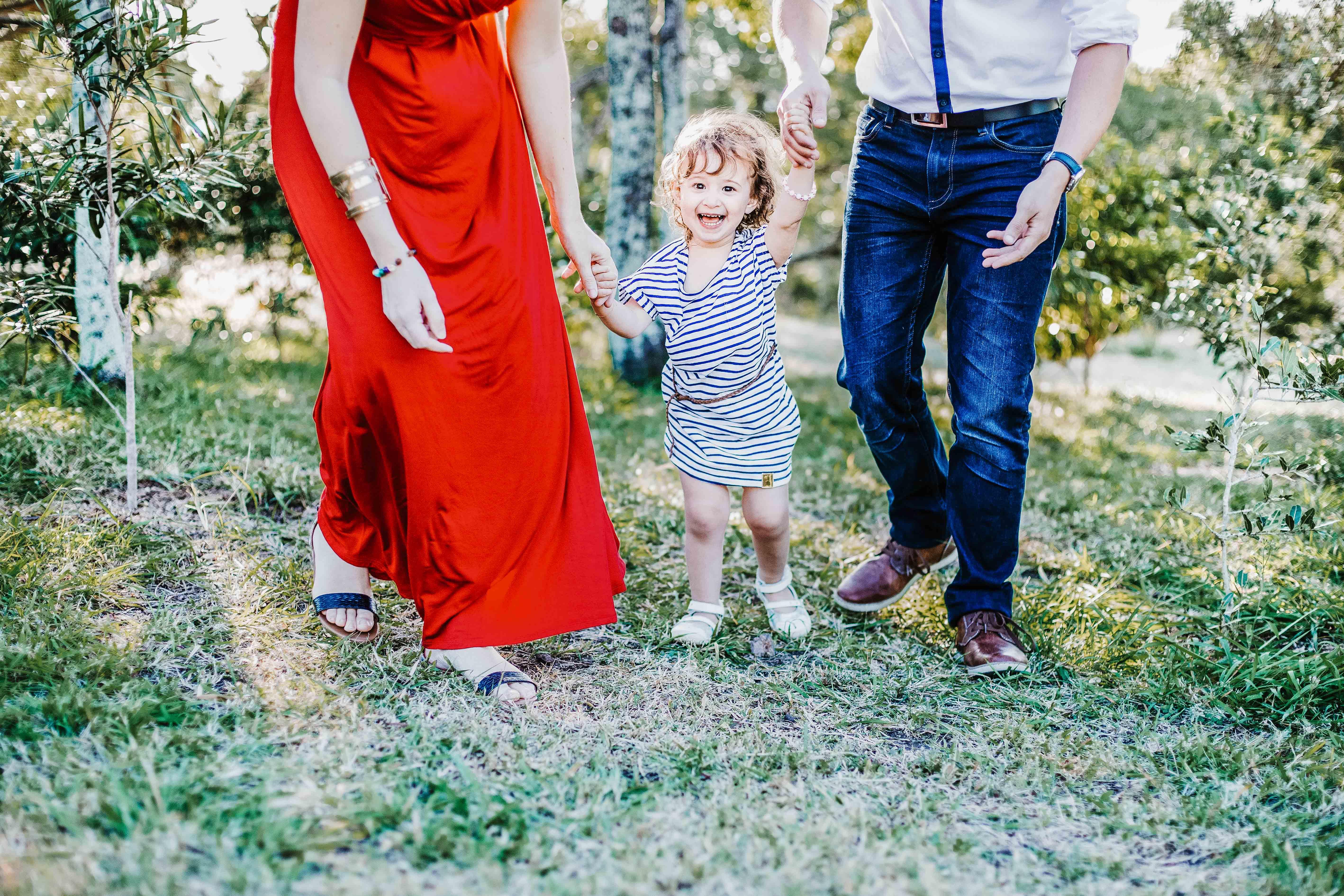 séance photo famille lifestyle en extérieur. Les parents aident la petite fille à marcher, ils lui tiennent la main et marchent dans l'herbe