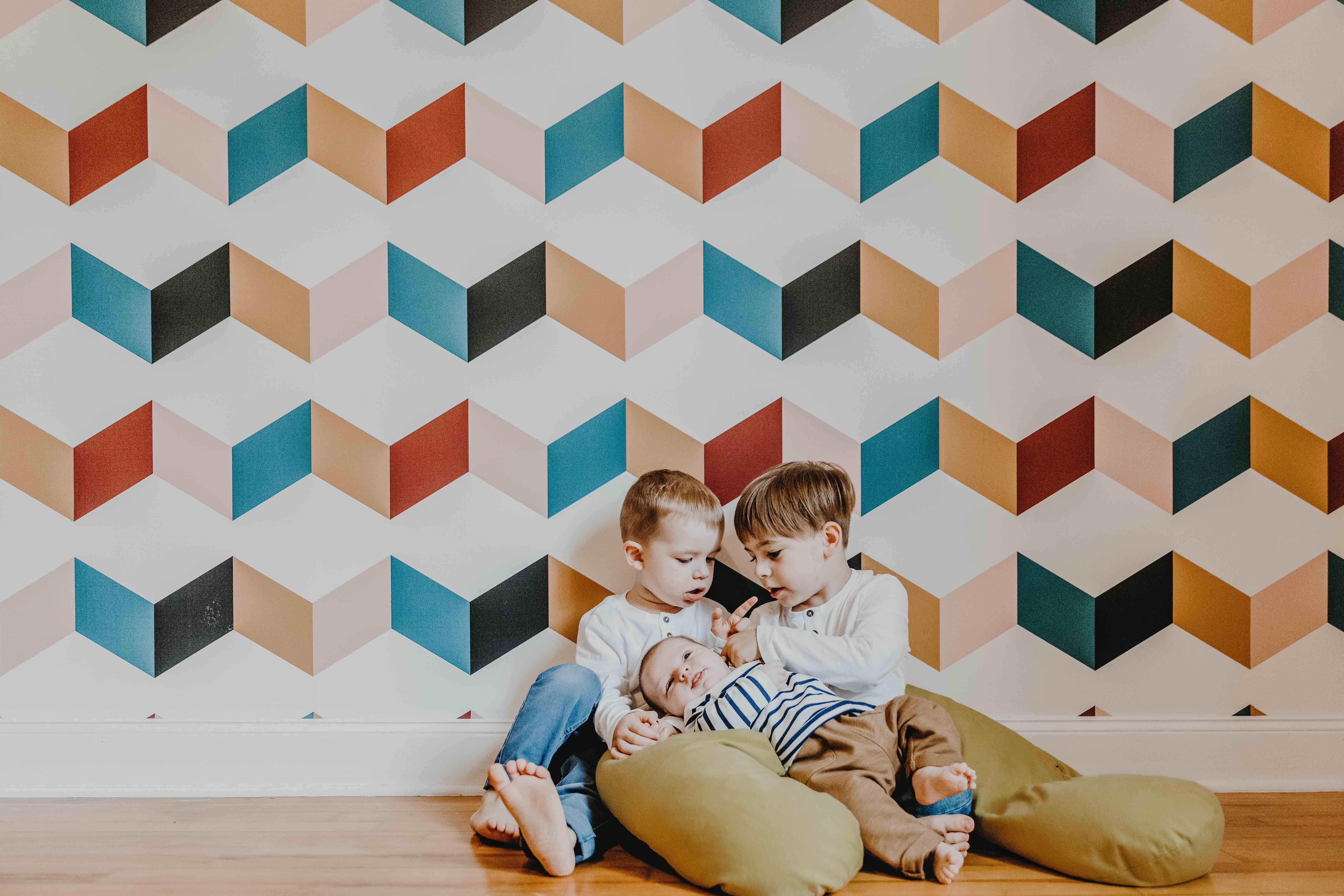 séance photo famille lifestyle à domicile. les enfants sont assis par terre contre un mur à tapisserie graphique et colorée. les grands frère tiennent bébé dans leurs bras et le regardent