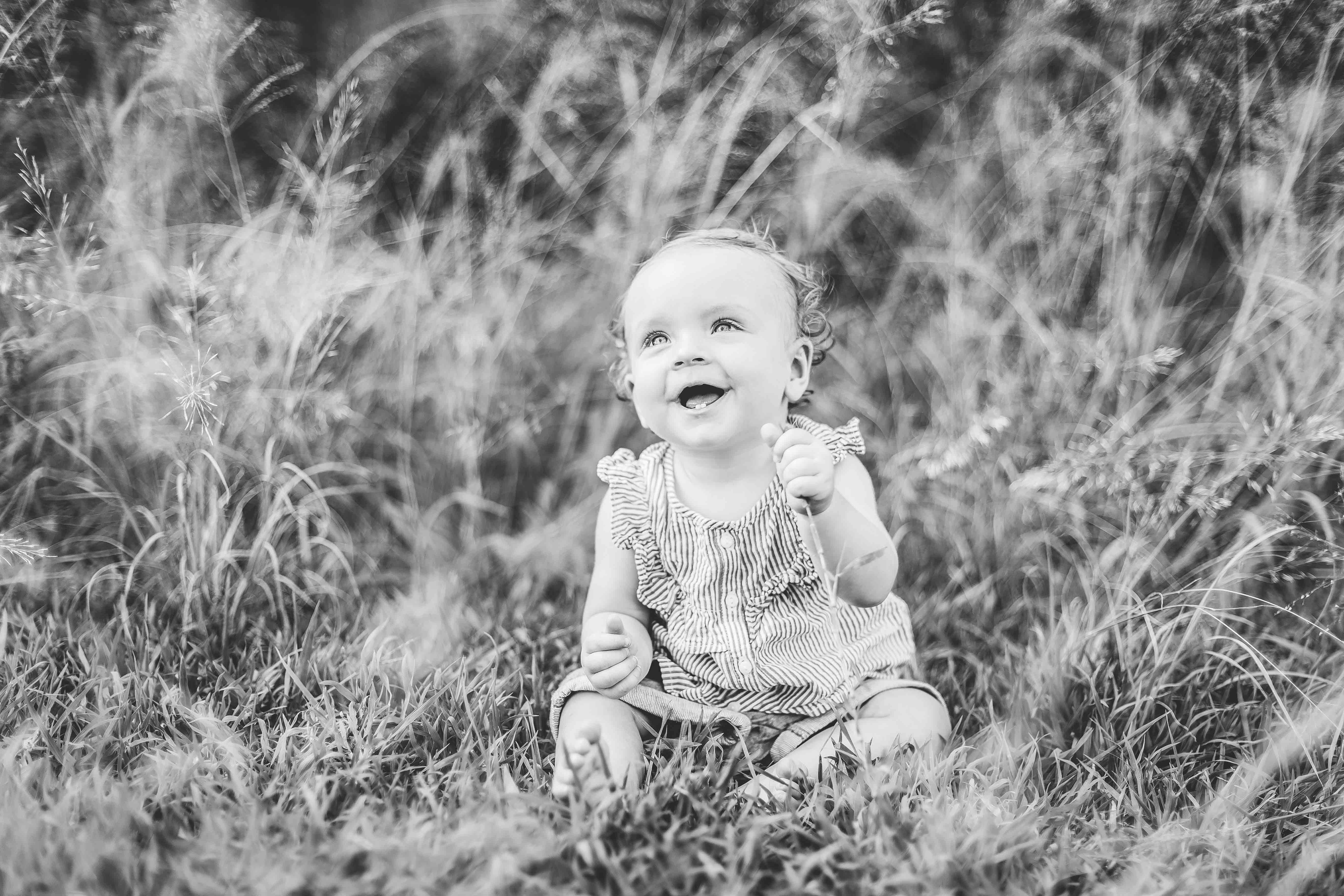 séance photo en extérieur lifestyle. une petite fille assise dans l'herbe, rigole regarde vers le ciel. photo noir et blanc
