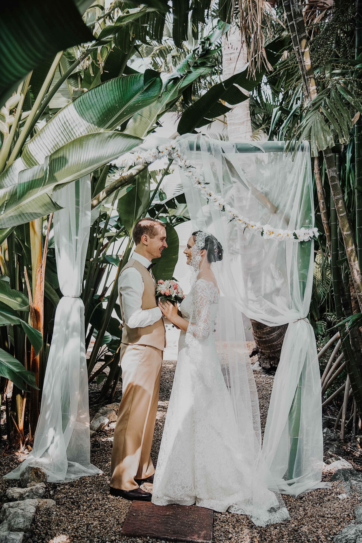 cérémonie de mariage elopement dans une forêt tropicale. les mariés sont face à face et se tiennent les mains