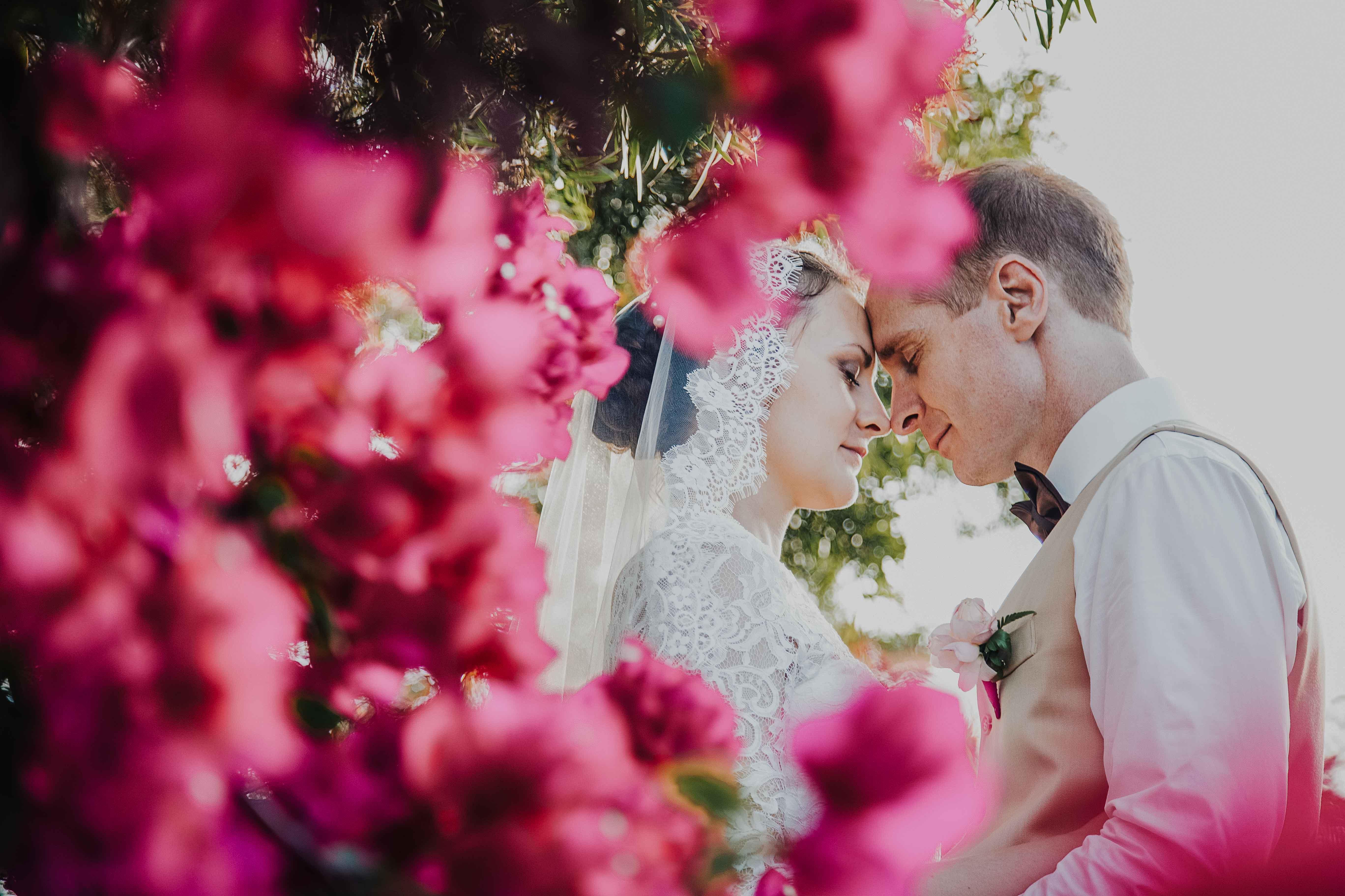 les mariés sont enlacés, tête à tête, les yeux fermés. en premiers plan des fleurs roses