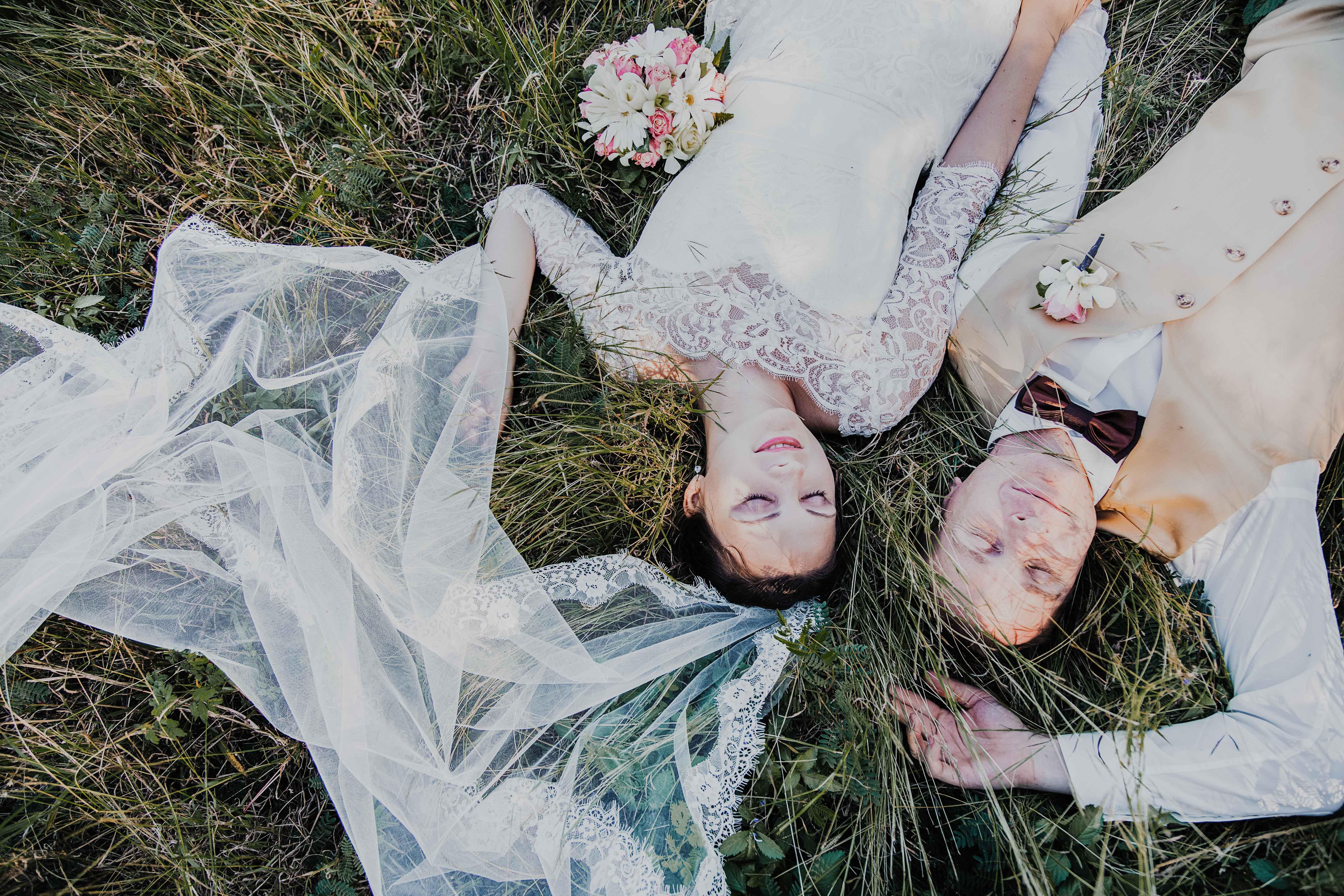 les mariés sont allongés dans les hautes herbes, les yeux fermés, mais dans la main. mariage champêtre et romantique