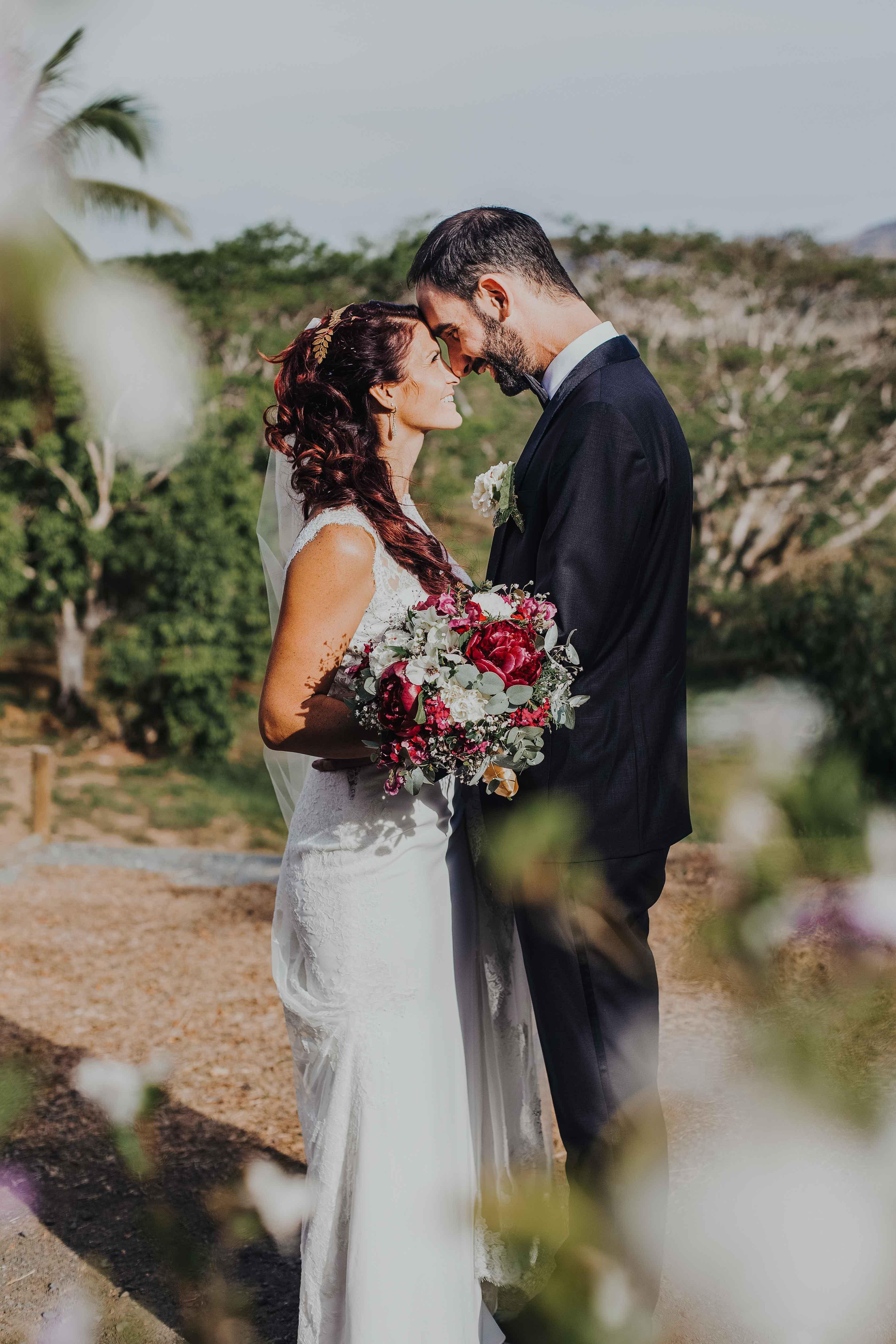les mariés sont tête à tête, se regardent en souriant, dans la nature, le soleil les couche