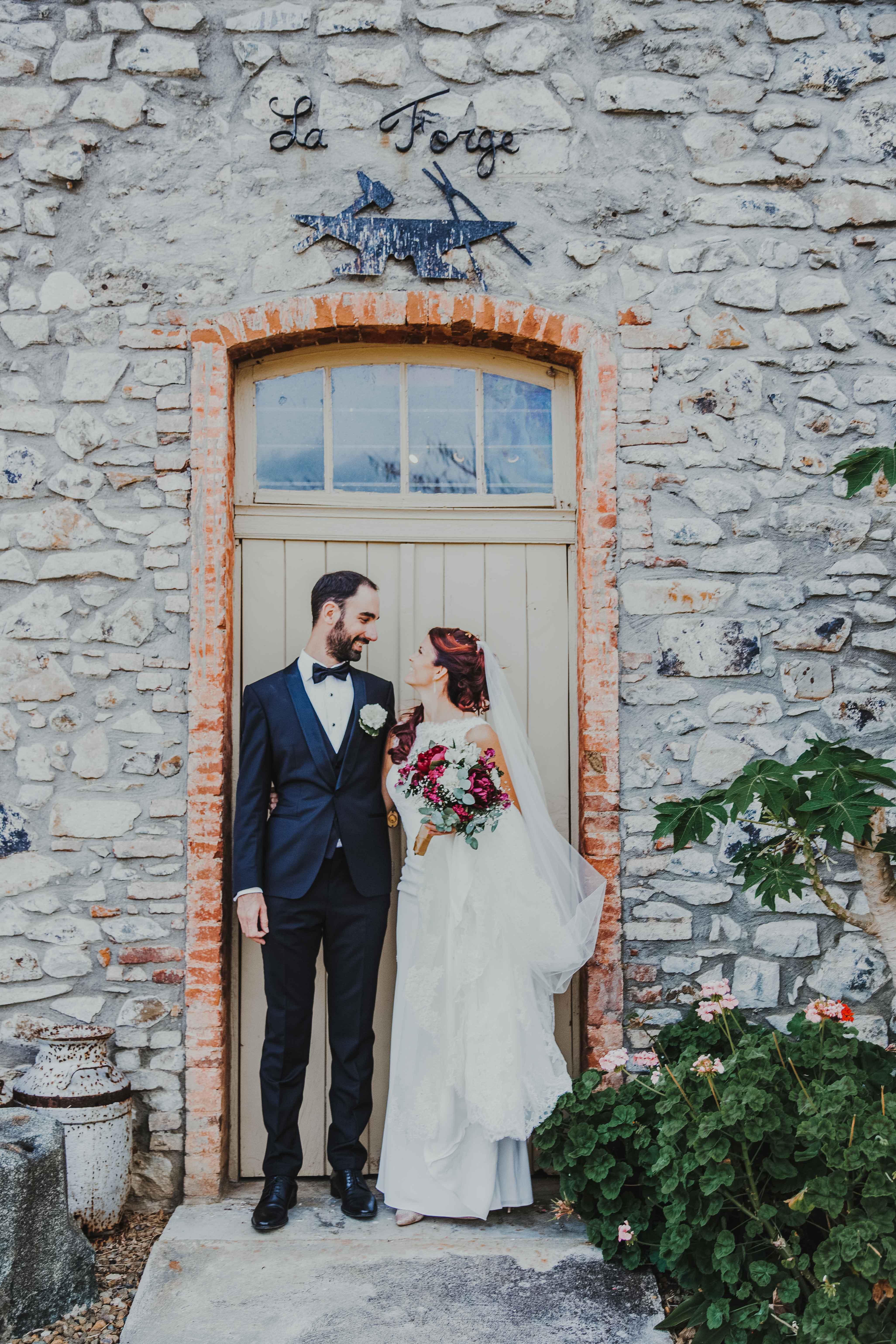 couple de mariés sous une porte rustique d'un bâtiment en pierre, les mariés se regardent et sourient