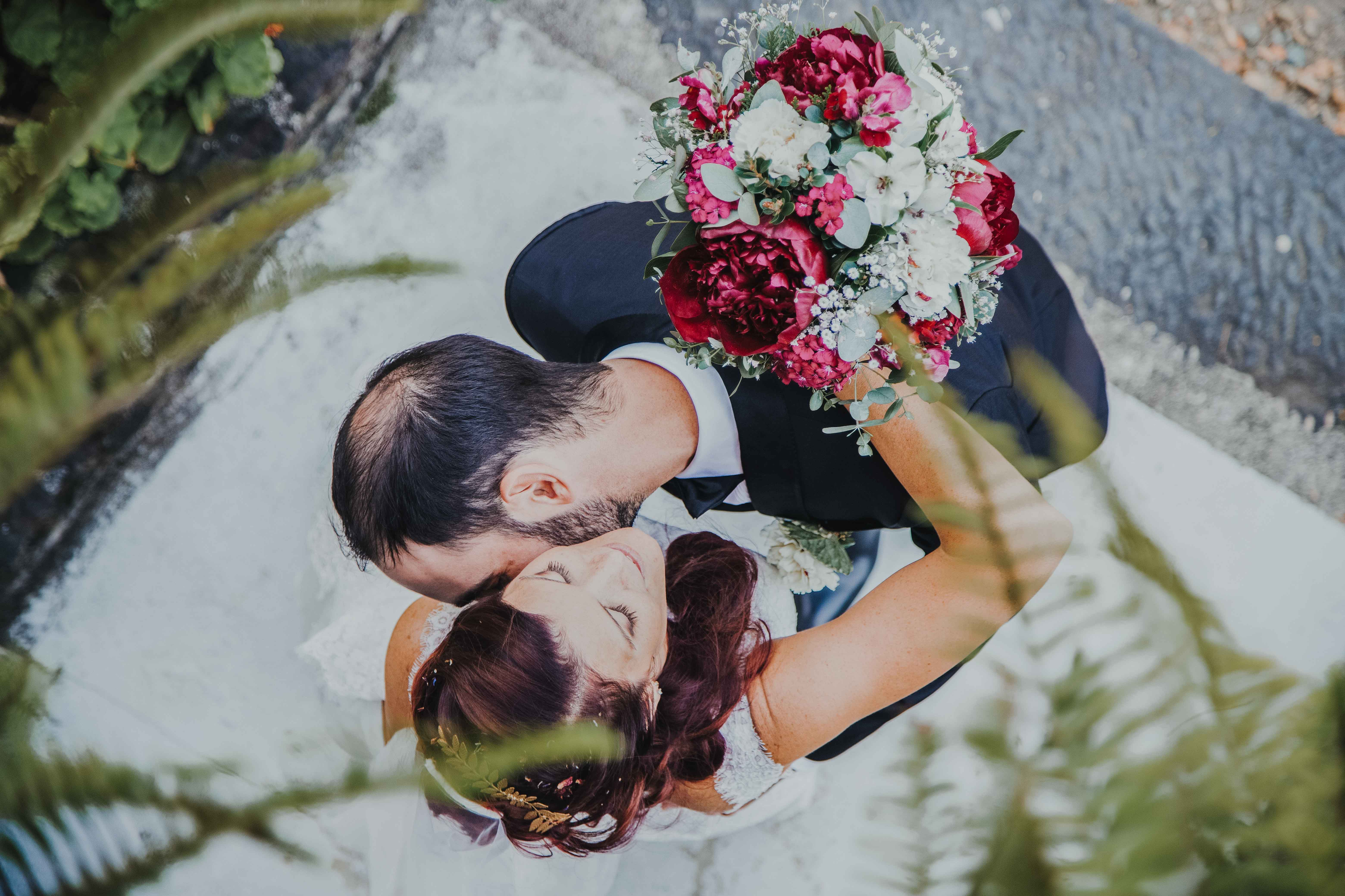 les mariés sont enlacés, vus du dessus, le mariés embrasse la mariée dans le cou
