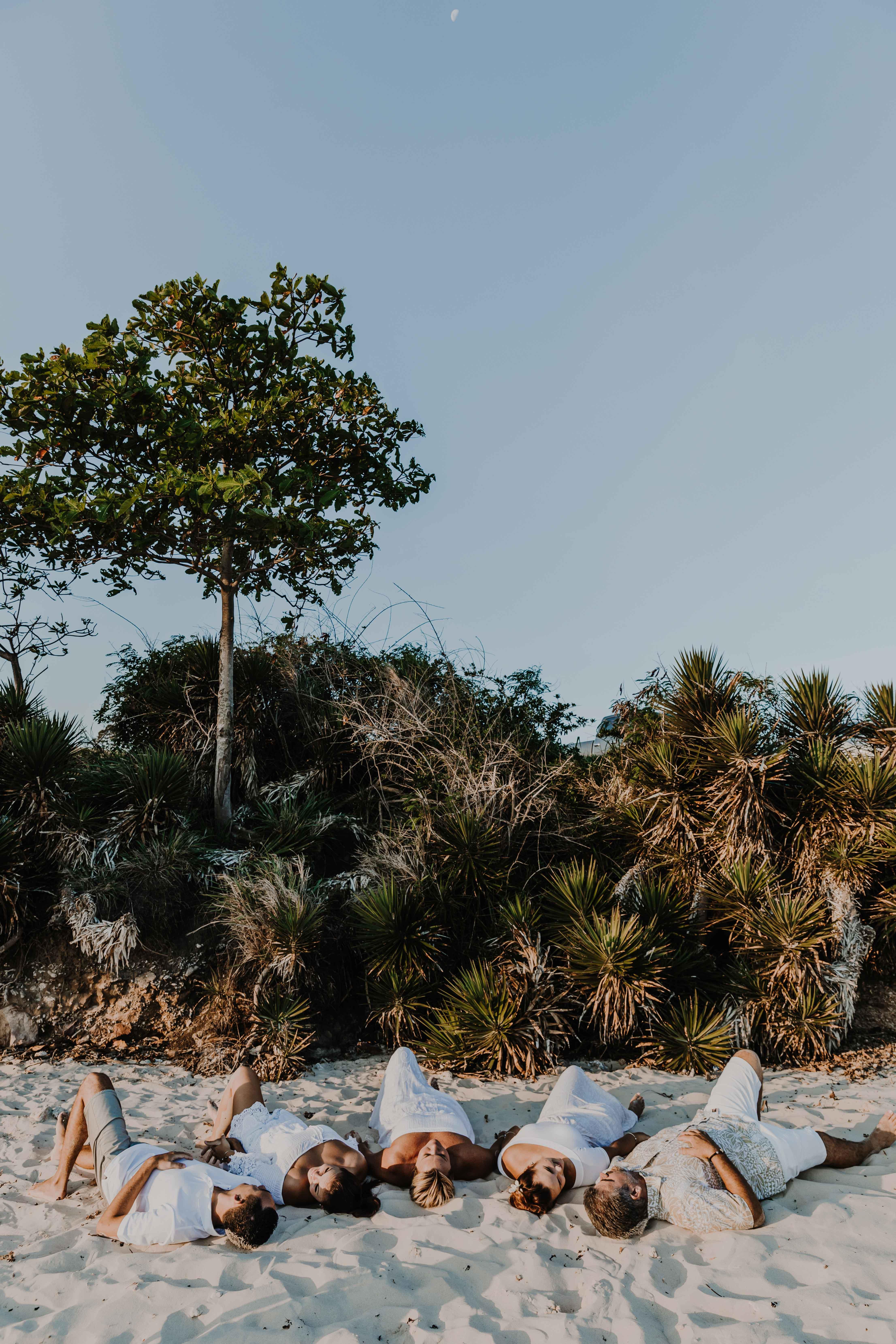 une famille allongée dans le sable au coucher du soleil