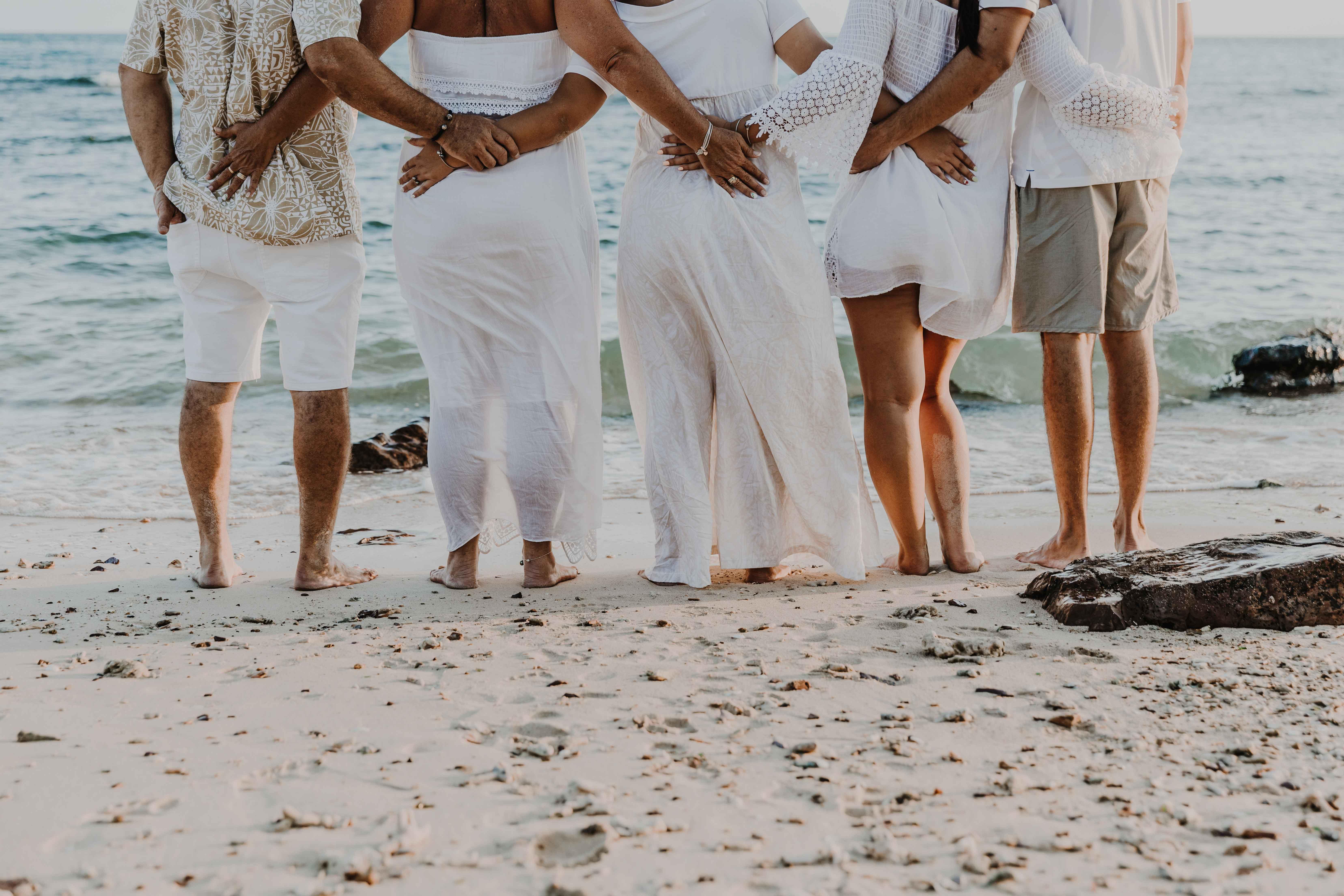 la famille est de dos, tout le monde est bras dessus bras dessous et regarde la mer