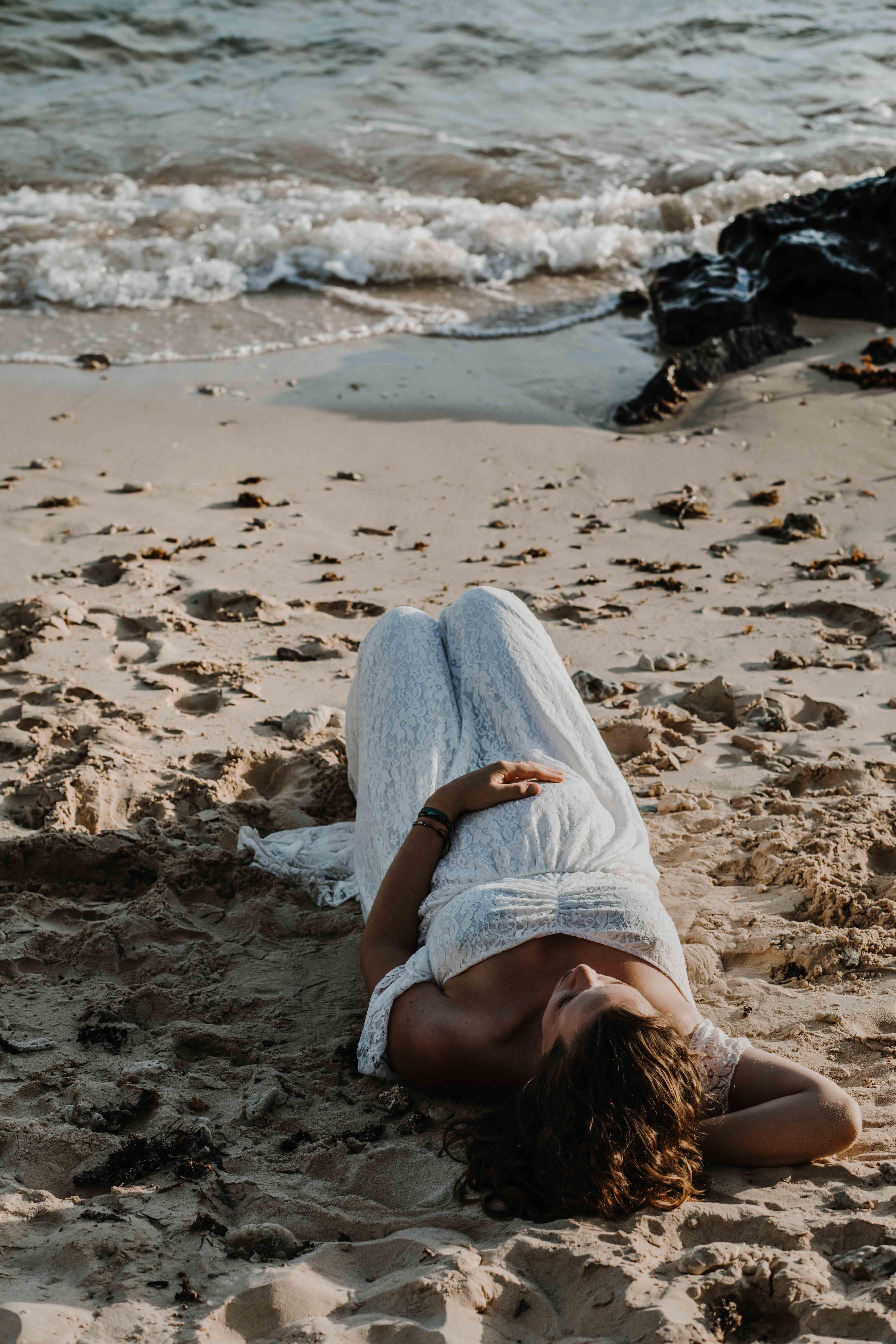 la femme enceinte est allongée sur la plage, sur le dos, la main posée sur son ventre rond