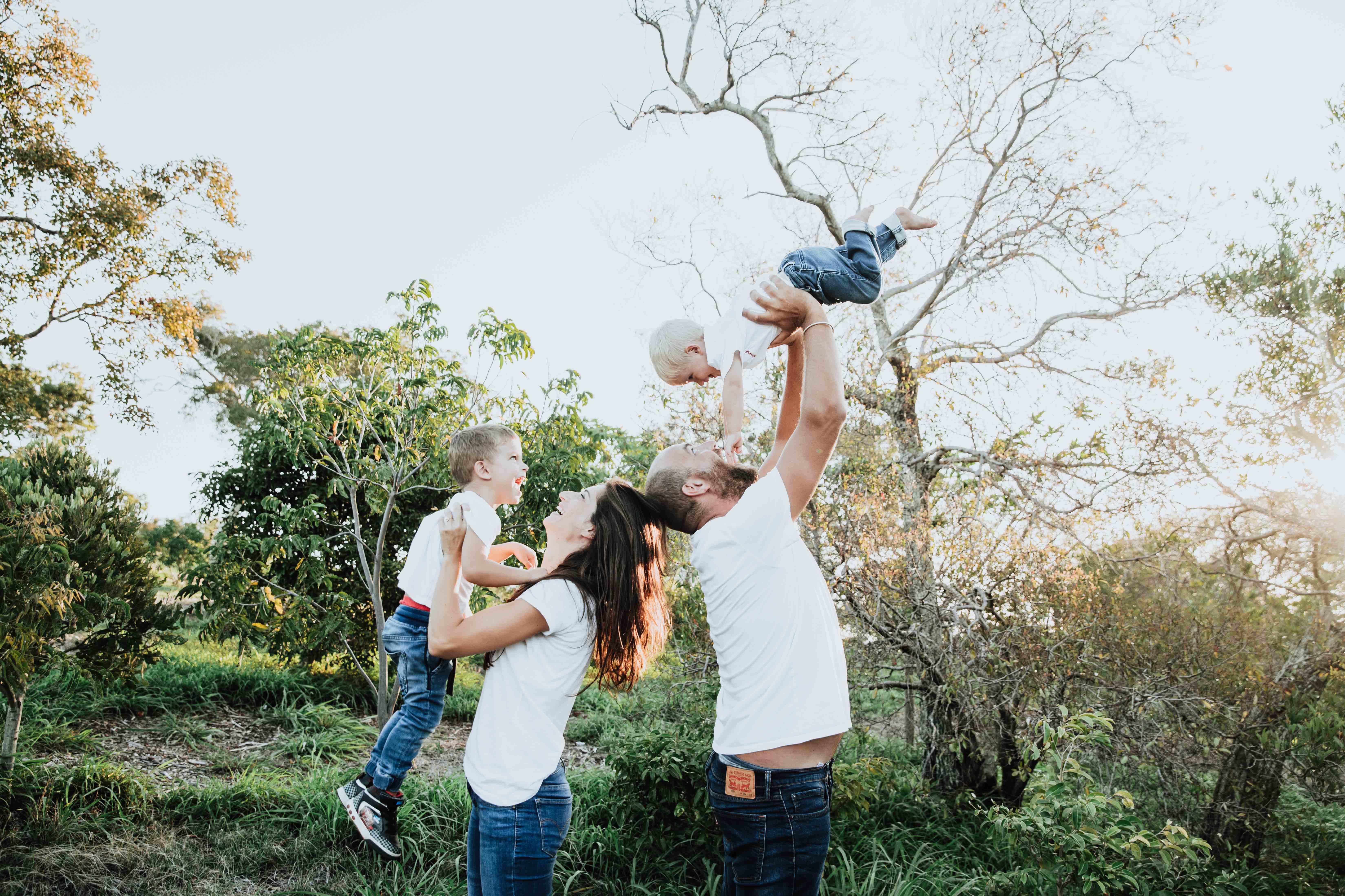 séance photo lifestyle en famille en extérieur, au coucher au soleil dans la verdure. Les parents jouent avec enfants. Les parents sont dos à dos, et soulèvent les enfants dans les airs