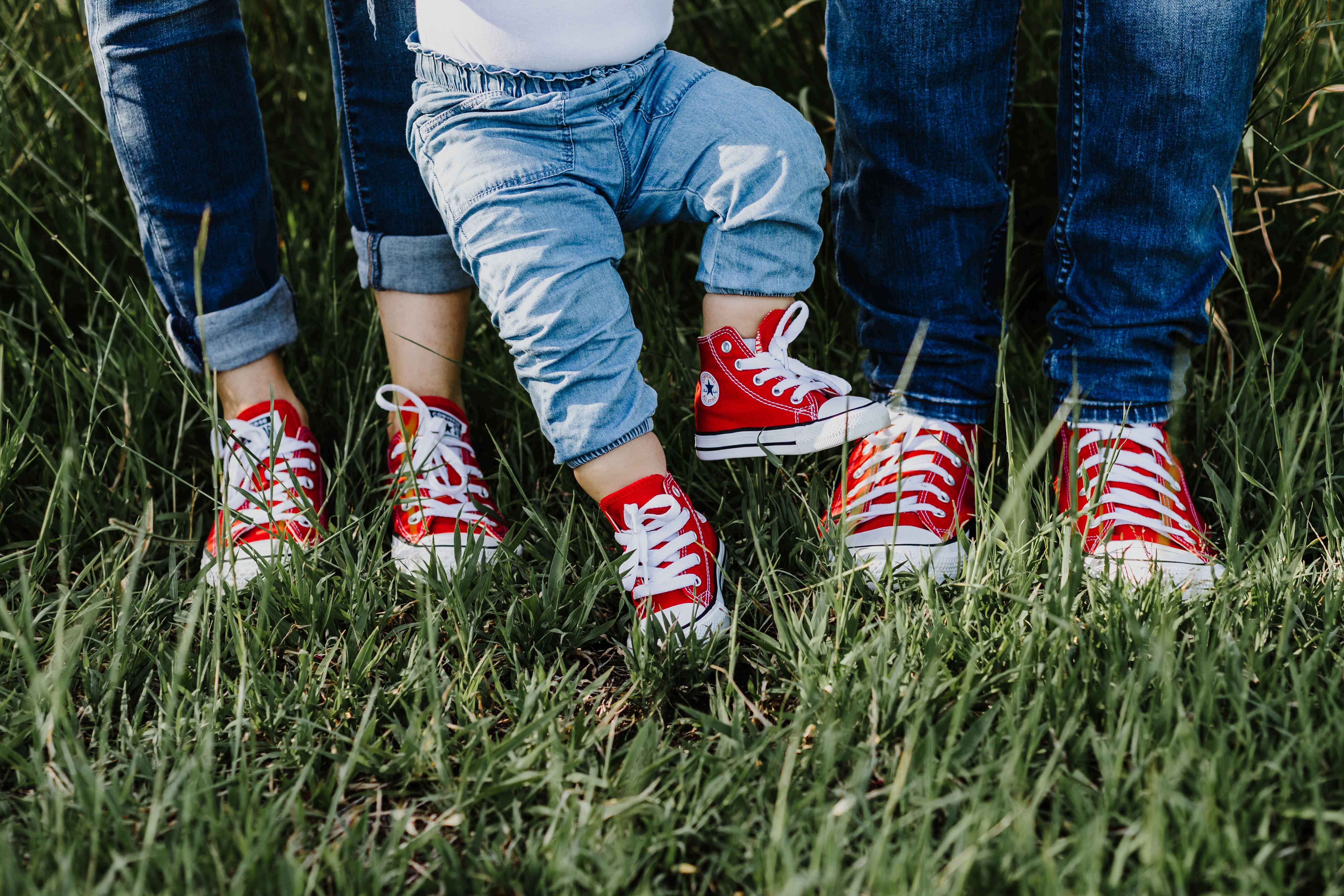 détail des chaussures, lors d'une séance photo famille en extérieur, dans la nature. Les parents et bébé portent des converse rouges.