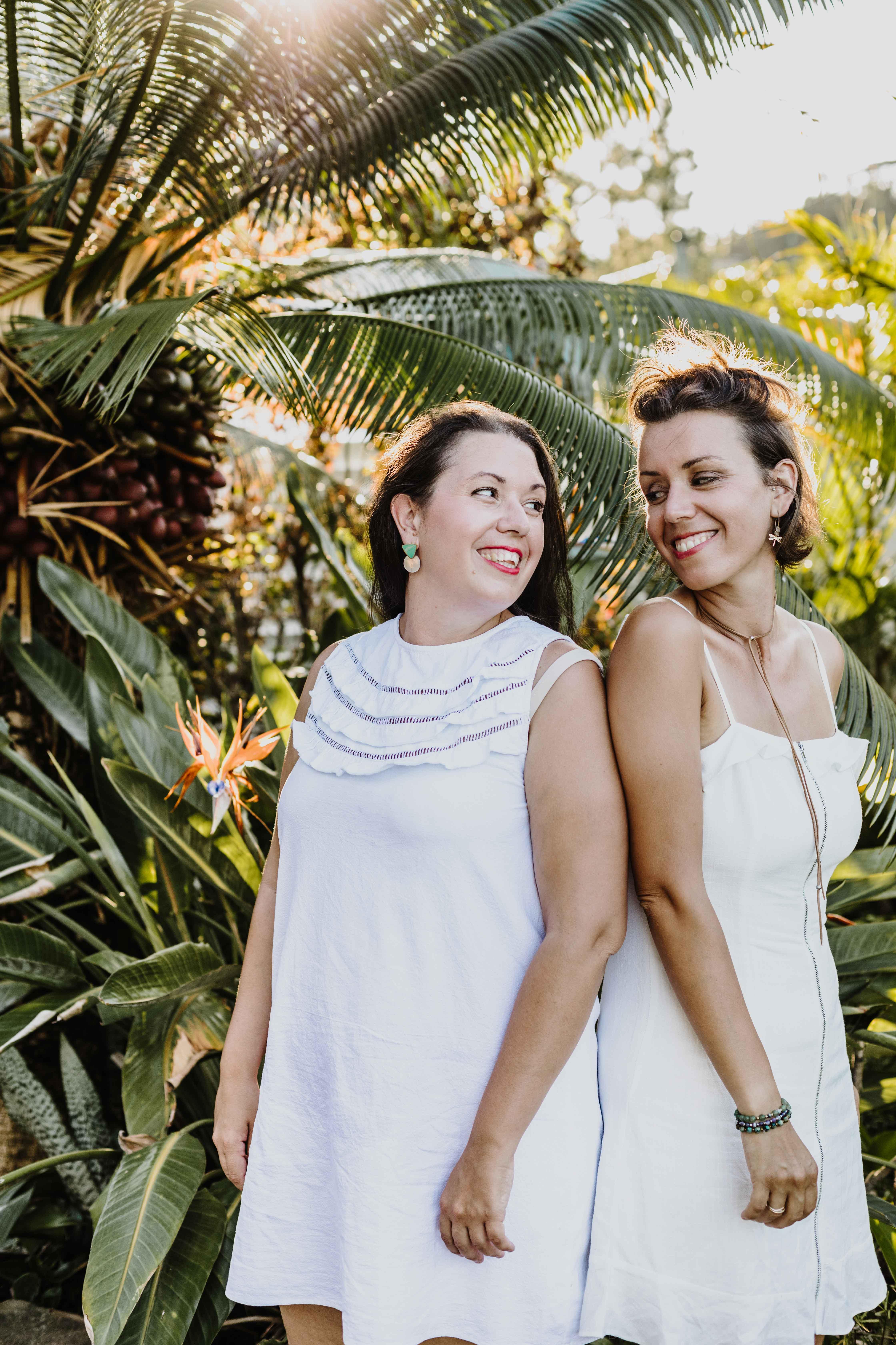 Deux soeurs habillées de blanc se regardent lors d'une séance photo à Nouméa, Nouvelle-Calédonie, France. Végétation tropicale et coucher de soleil.