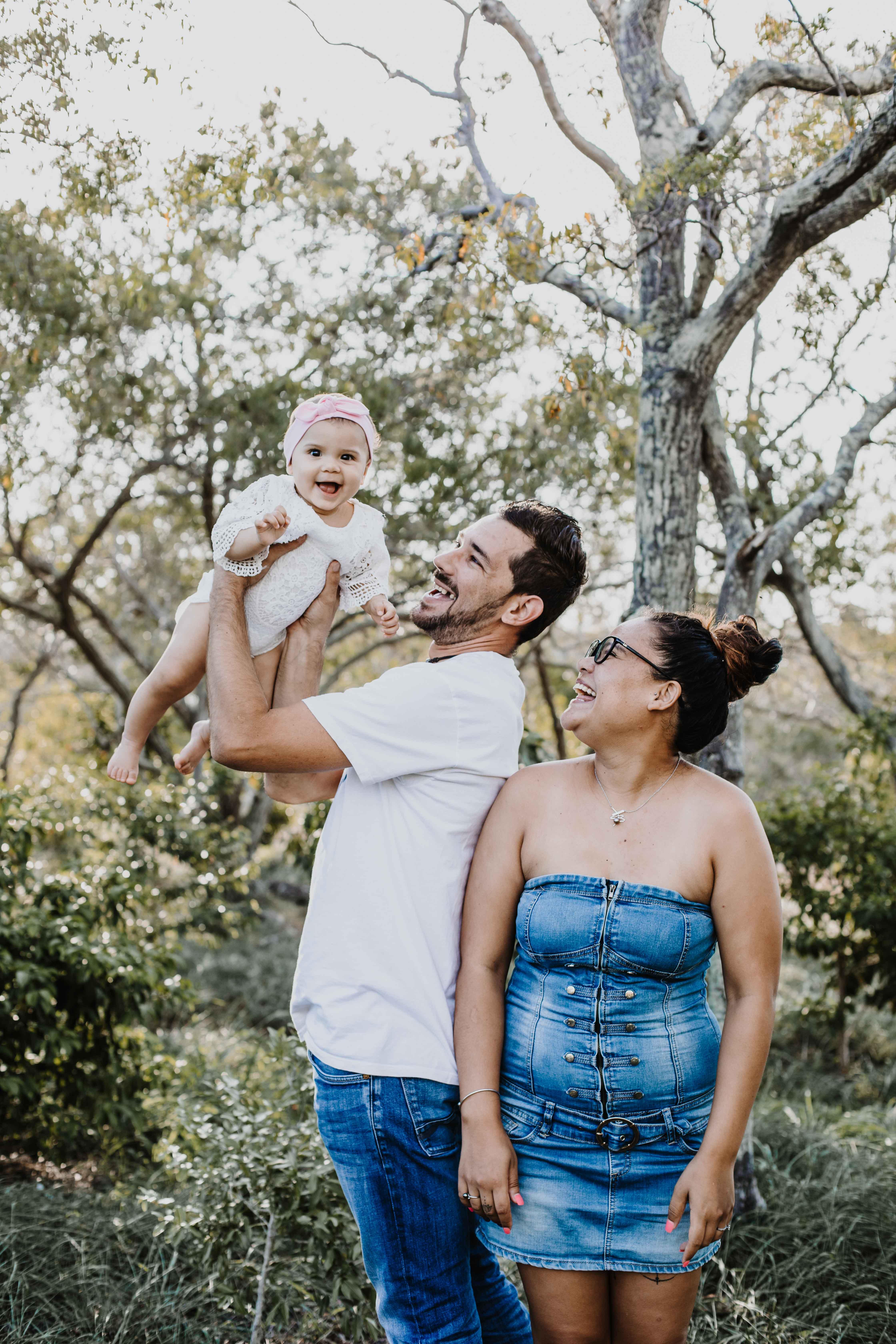 Dans la forêt, les parents jouent avec bébé lors de la séance photo famille. Papa lève bébé dans les airs, bébé rigole, les parents regardent la petite fille
