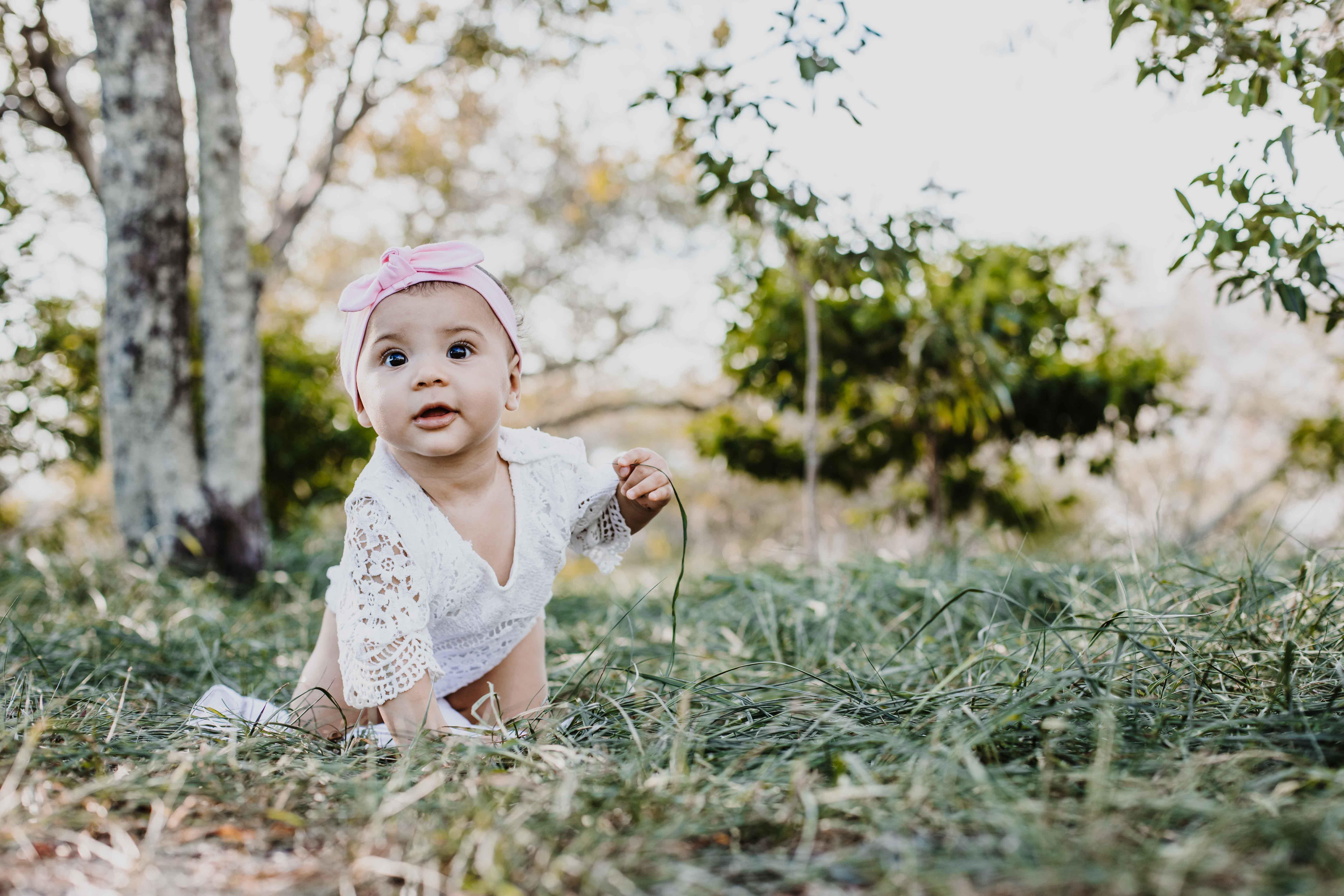 Un bébé marche à quatre pattes dans l'herbe. La petite fille porte une tenue blanche et un bandeau à cheveux rose
