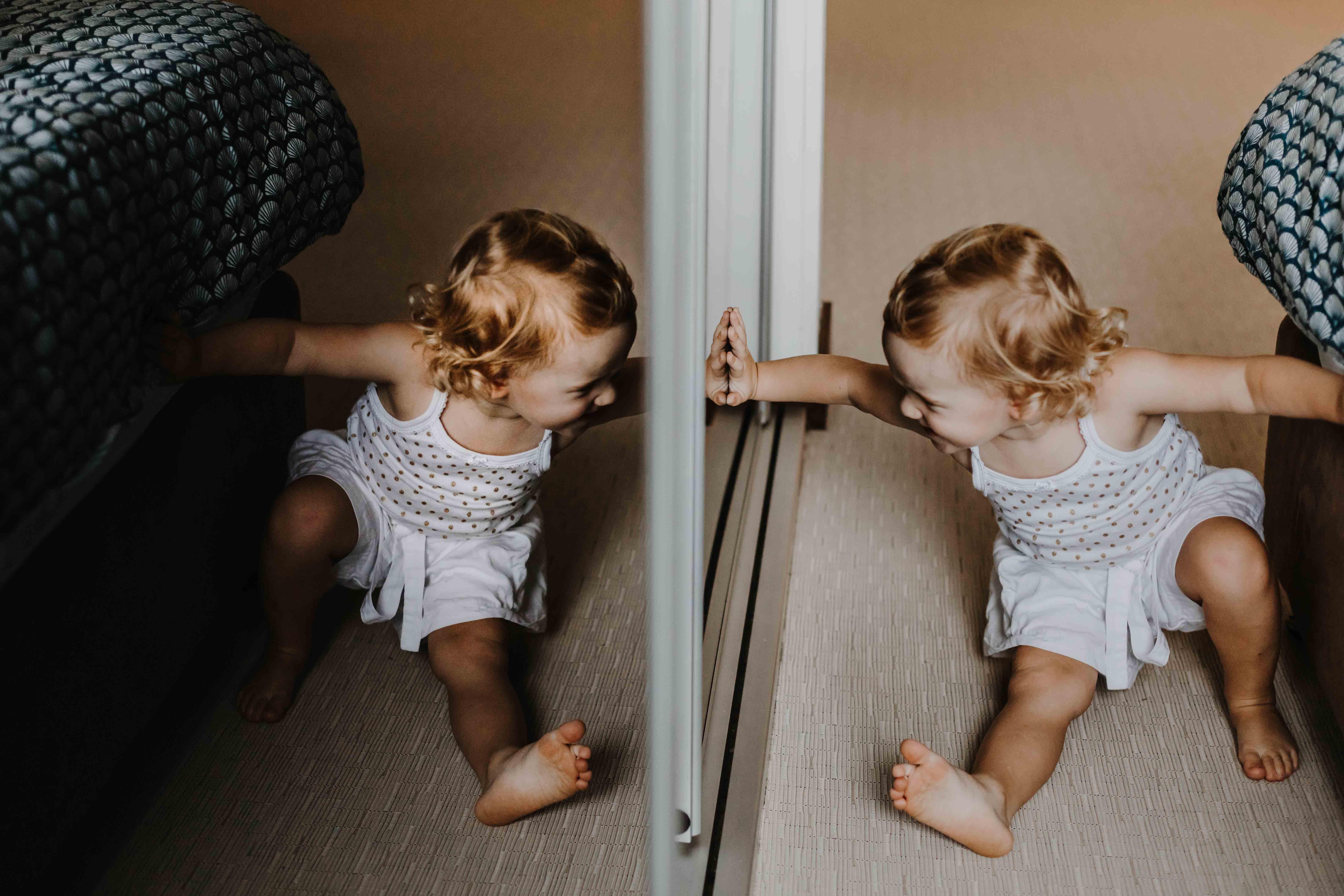 Petite fille qui joue dans la chambre, avec son reflet dans la vitre du placard