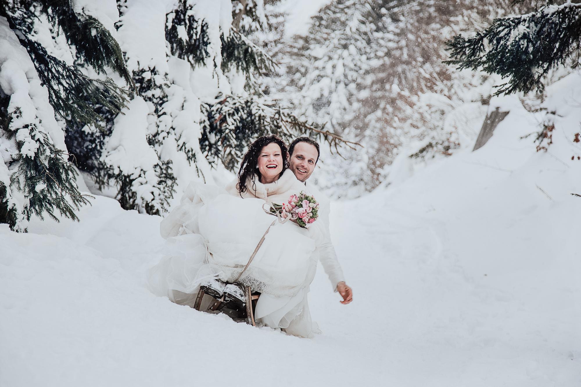 les mariés font de la luge dans la neige