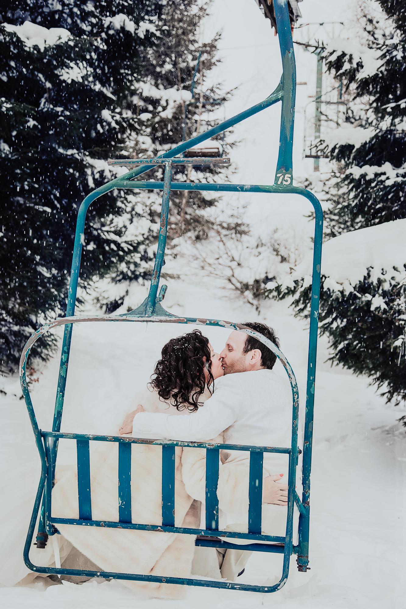 les mariés son assis sur un ancien télésiège et s'embrassent