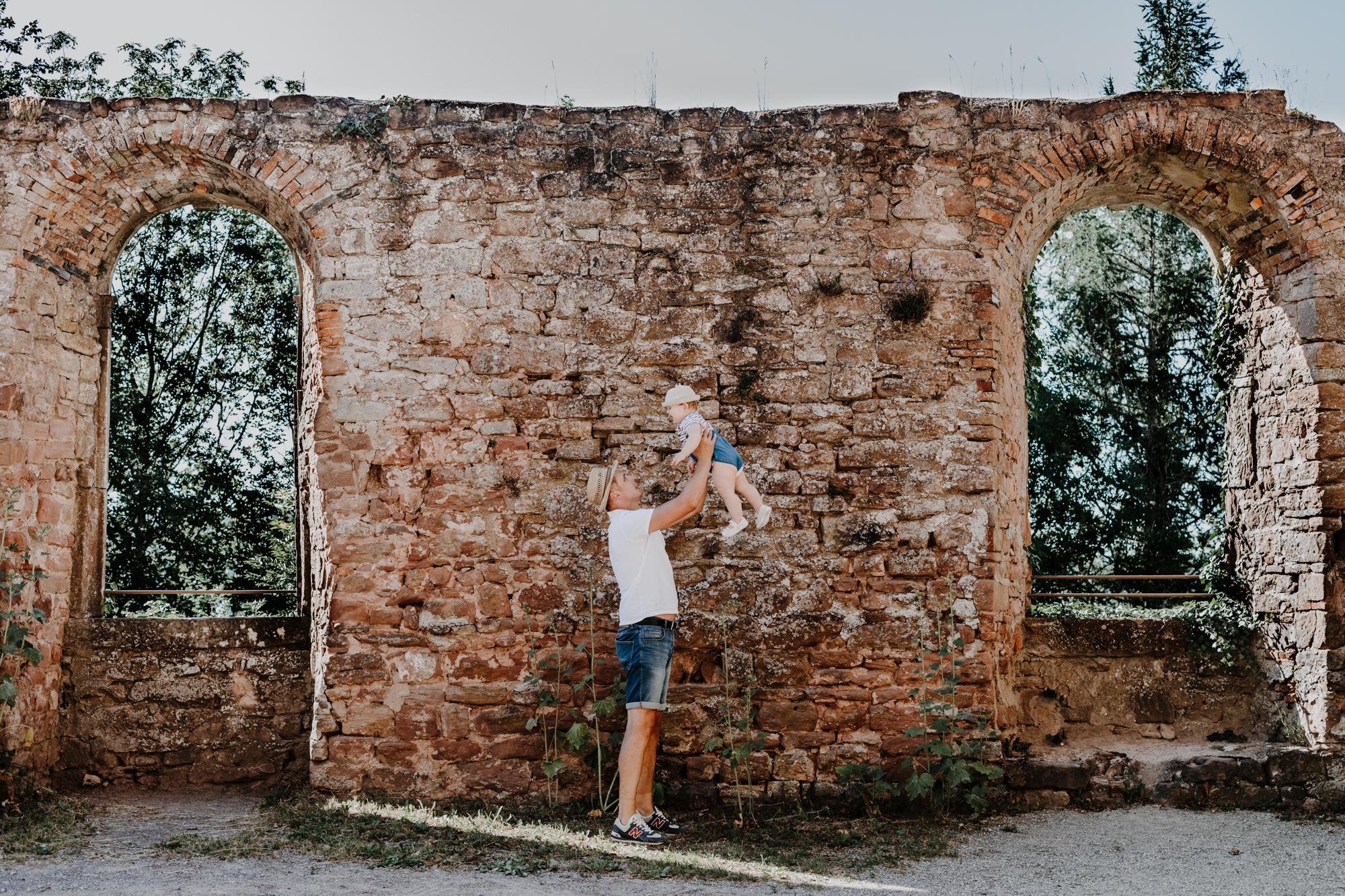 papa qui joue avec sa fille devant un mur en pierre des ruines d'un château