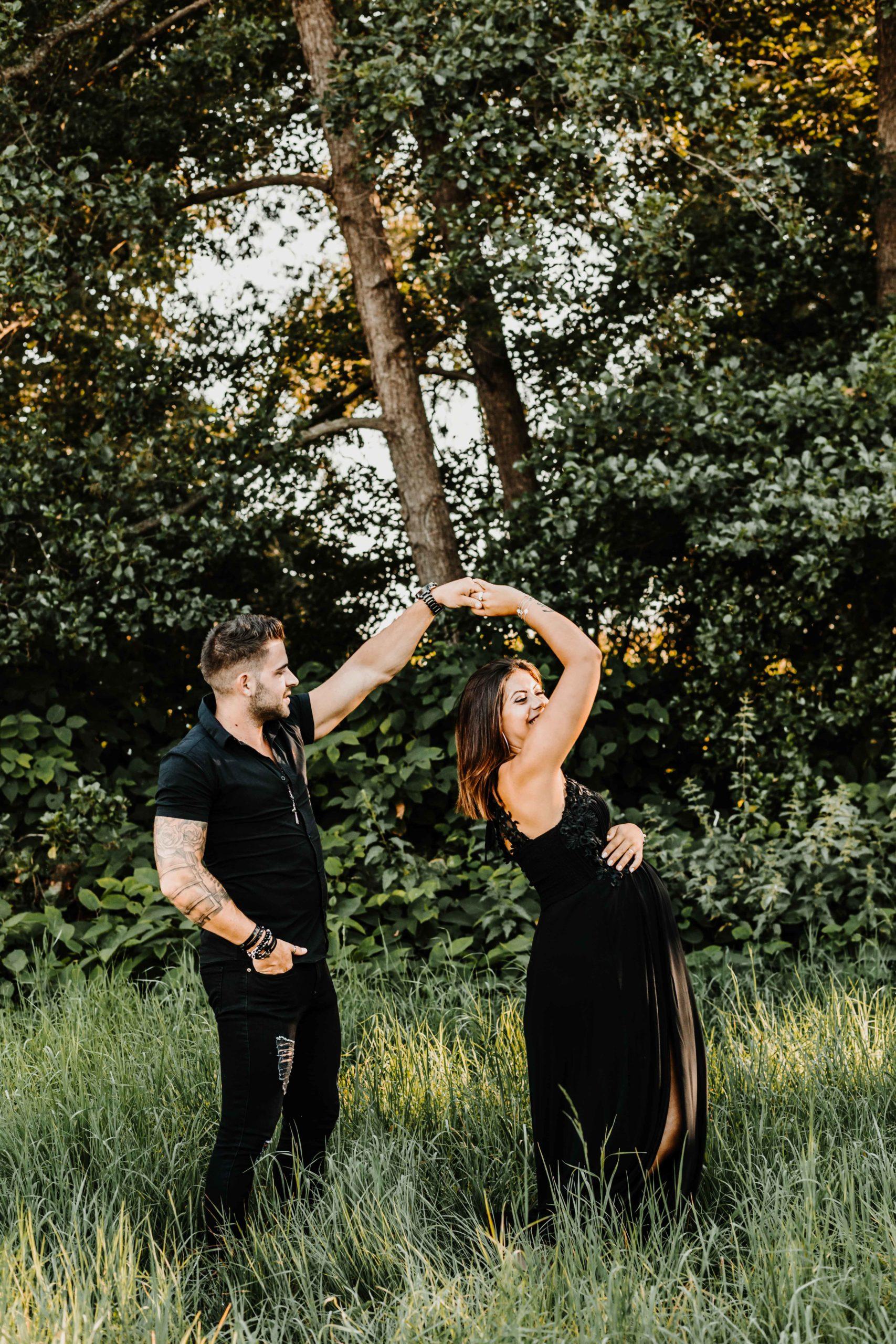 couple qui danse dans la nature, la femme est enceinte, lumière de coucher de soleil