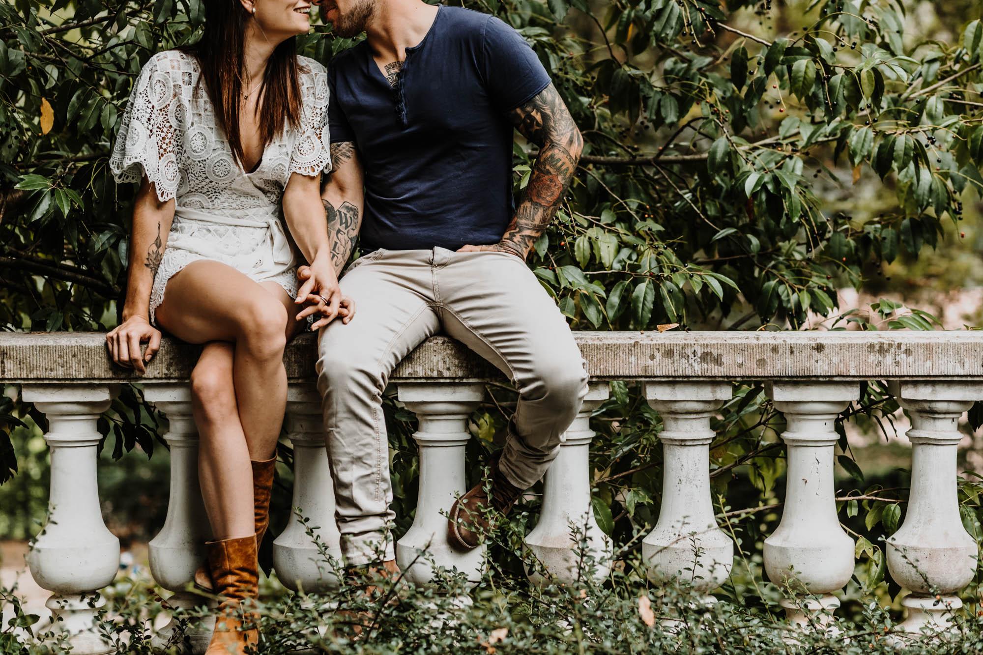 couple assis sur un muret se tient la main, s'embrassent