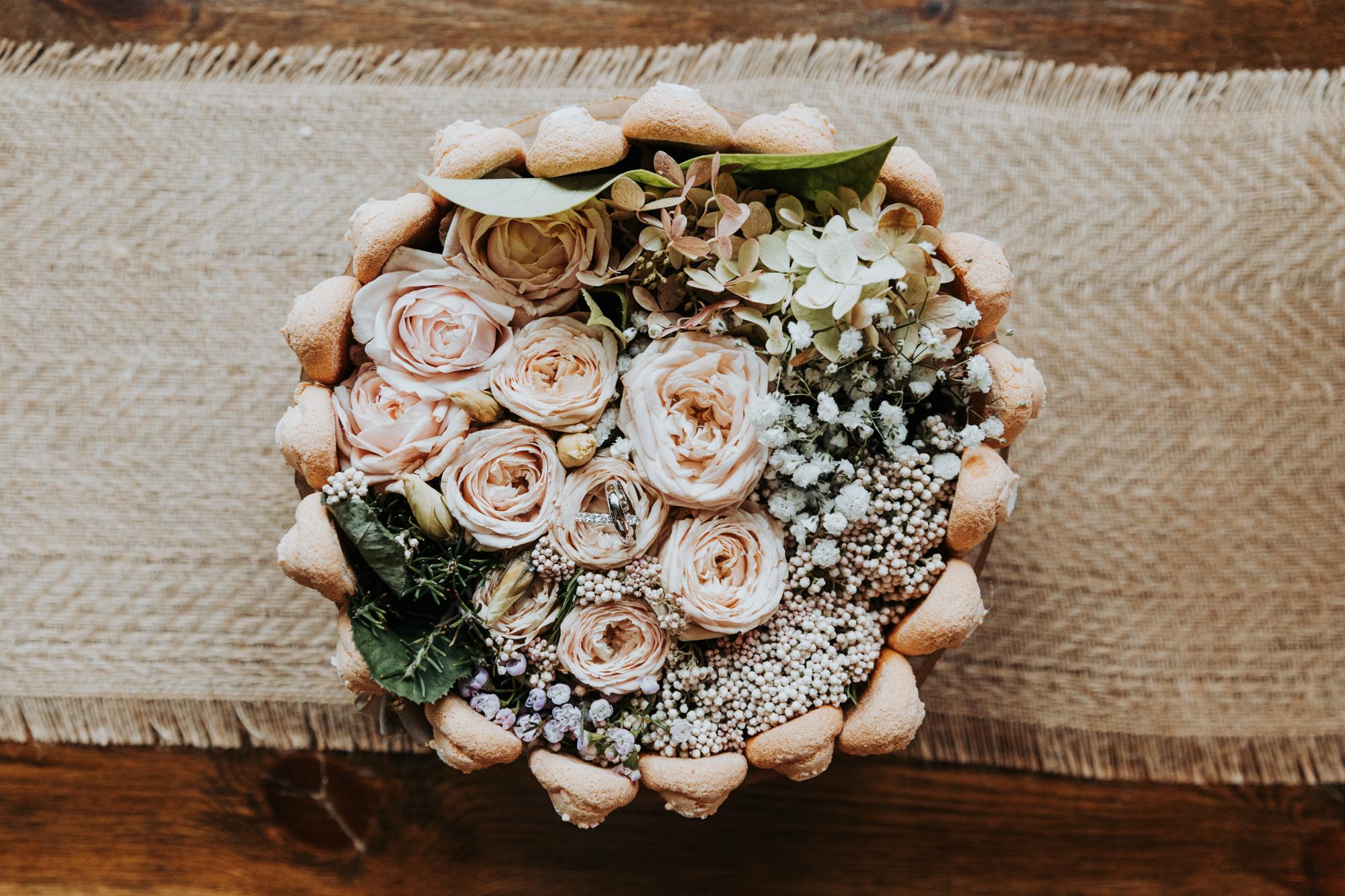 détail de décoration florale de mariage, les alliances sont posées dans les fleurs