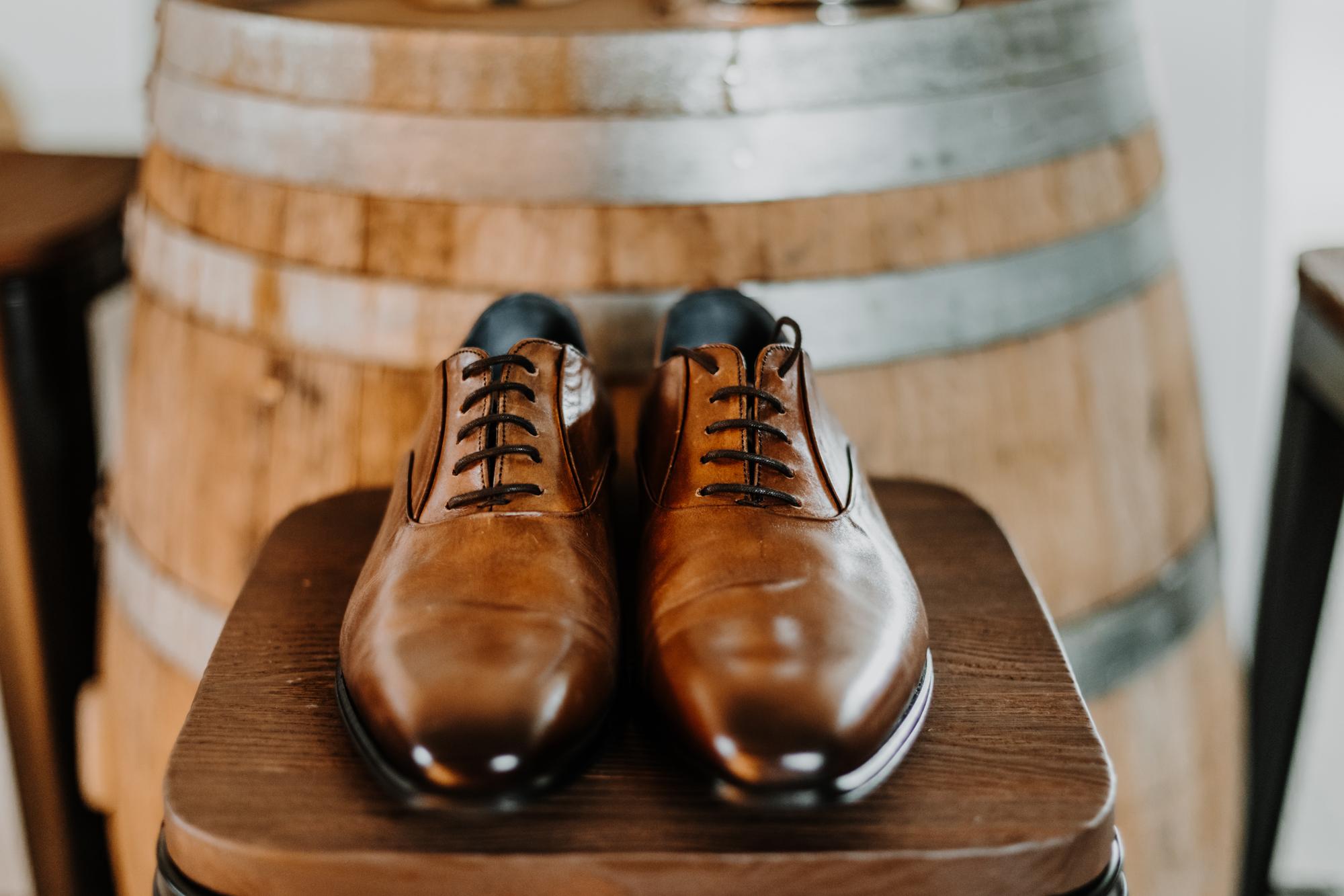 détail des chaussures du marié sur un tabouret, devant un tonneau