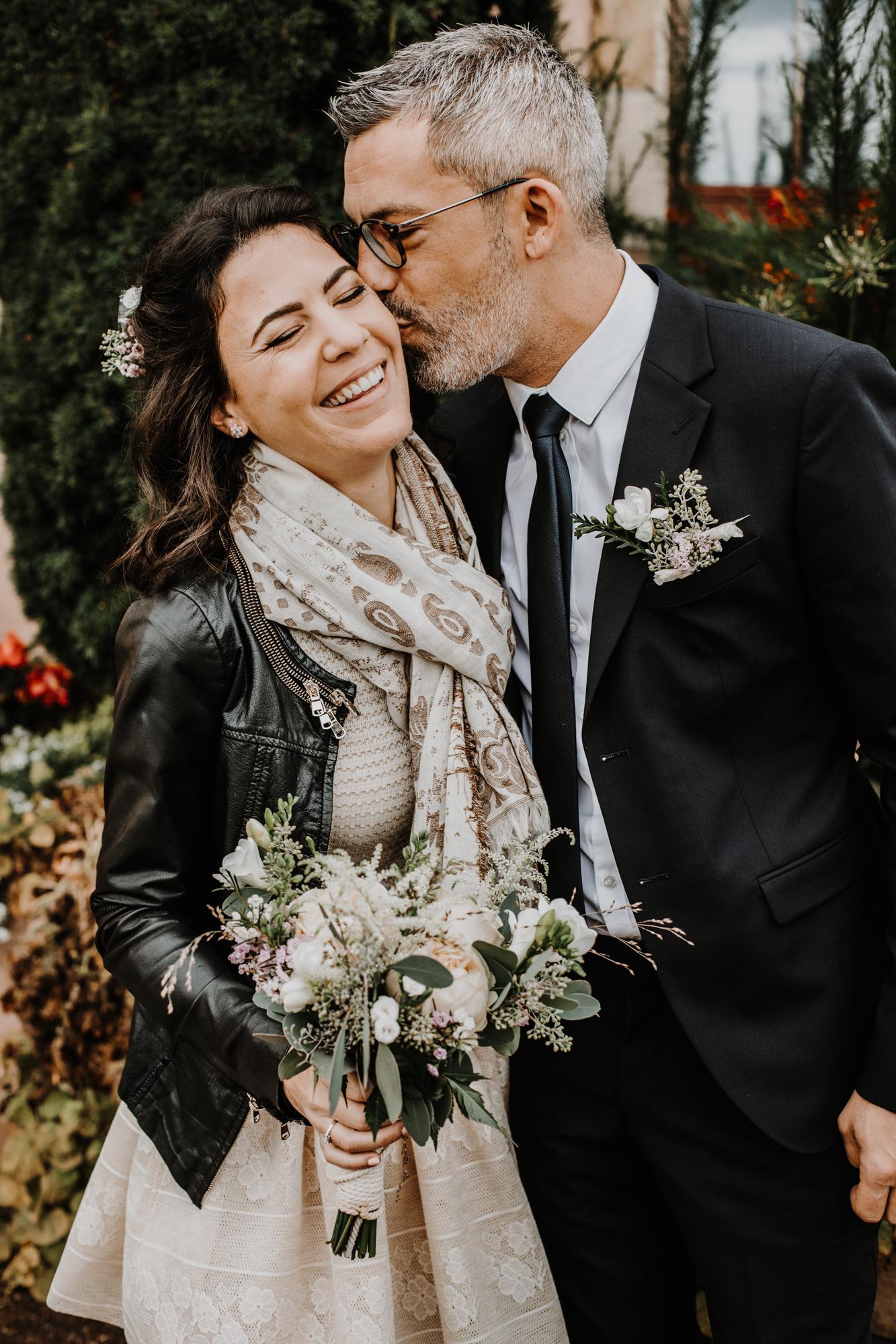 les mariés se retrouvent à la mairie, le marié embrasse la mariée sur la joue