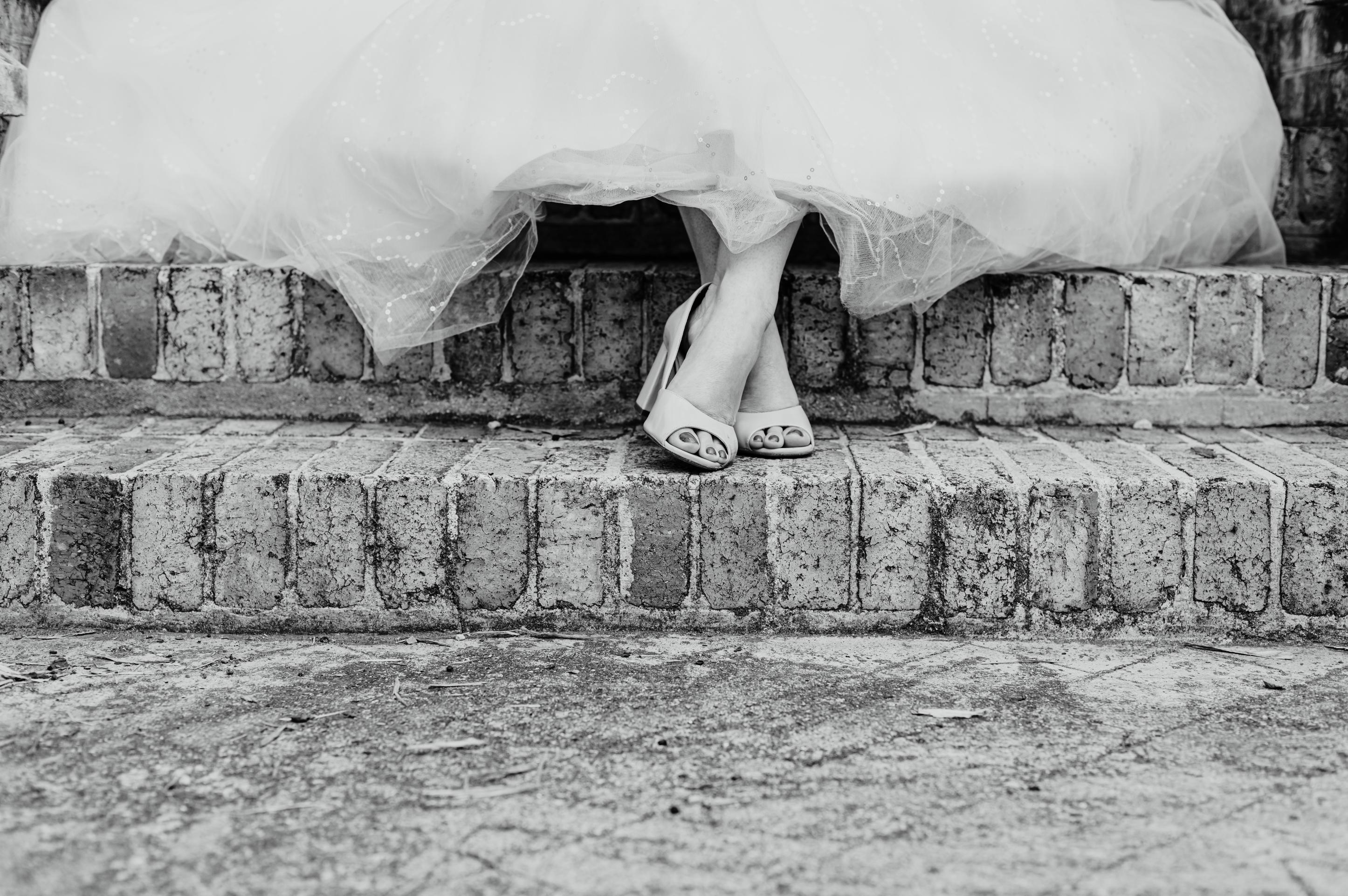 détail des pieds et chaussures de la mariés, assise sur des marches d'escalier en briques