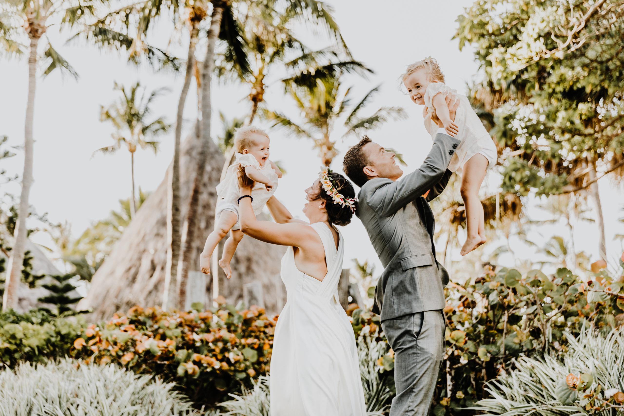 couple de mariés dos à do, portent chacun lui enfant dans les airs