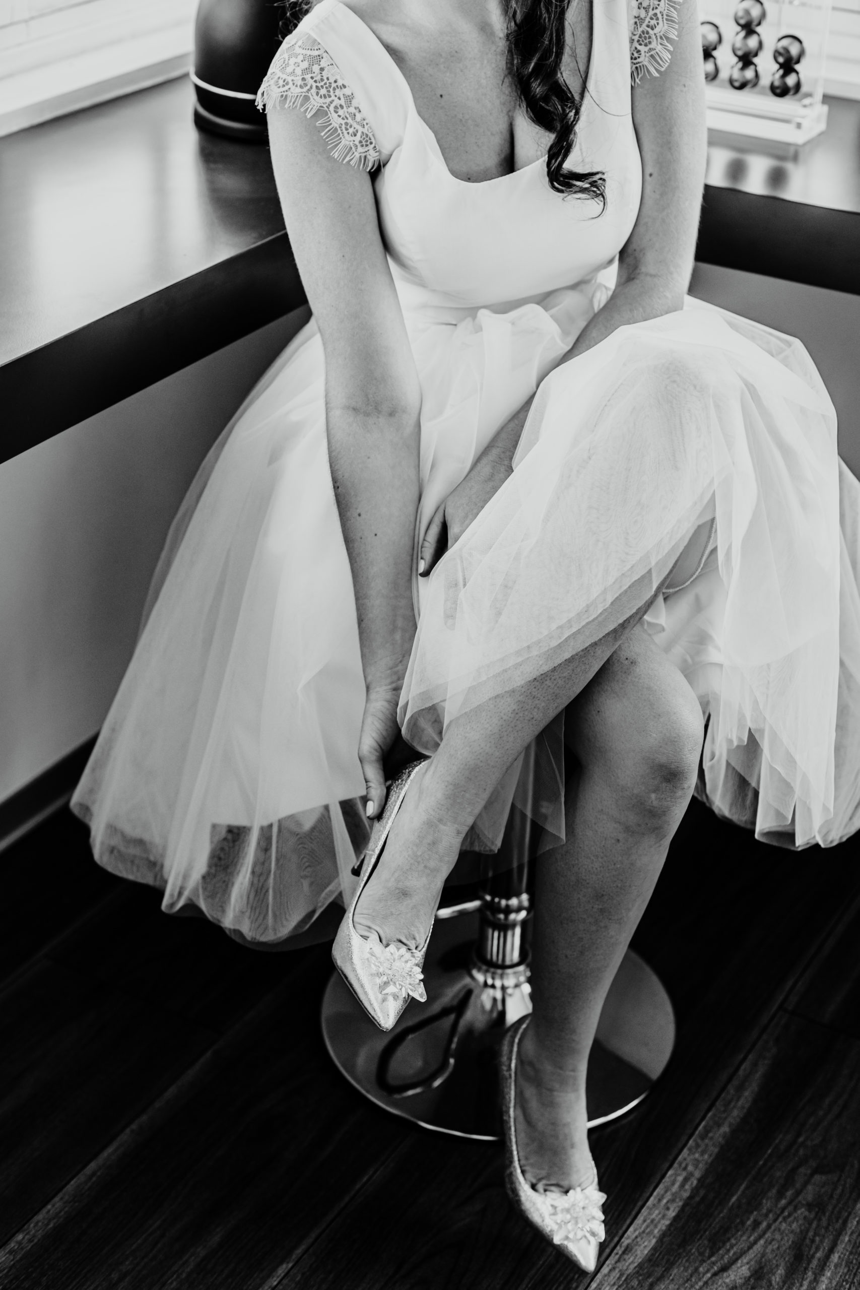 photo noir et blanc, la mariée assise met ses chaussures